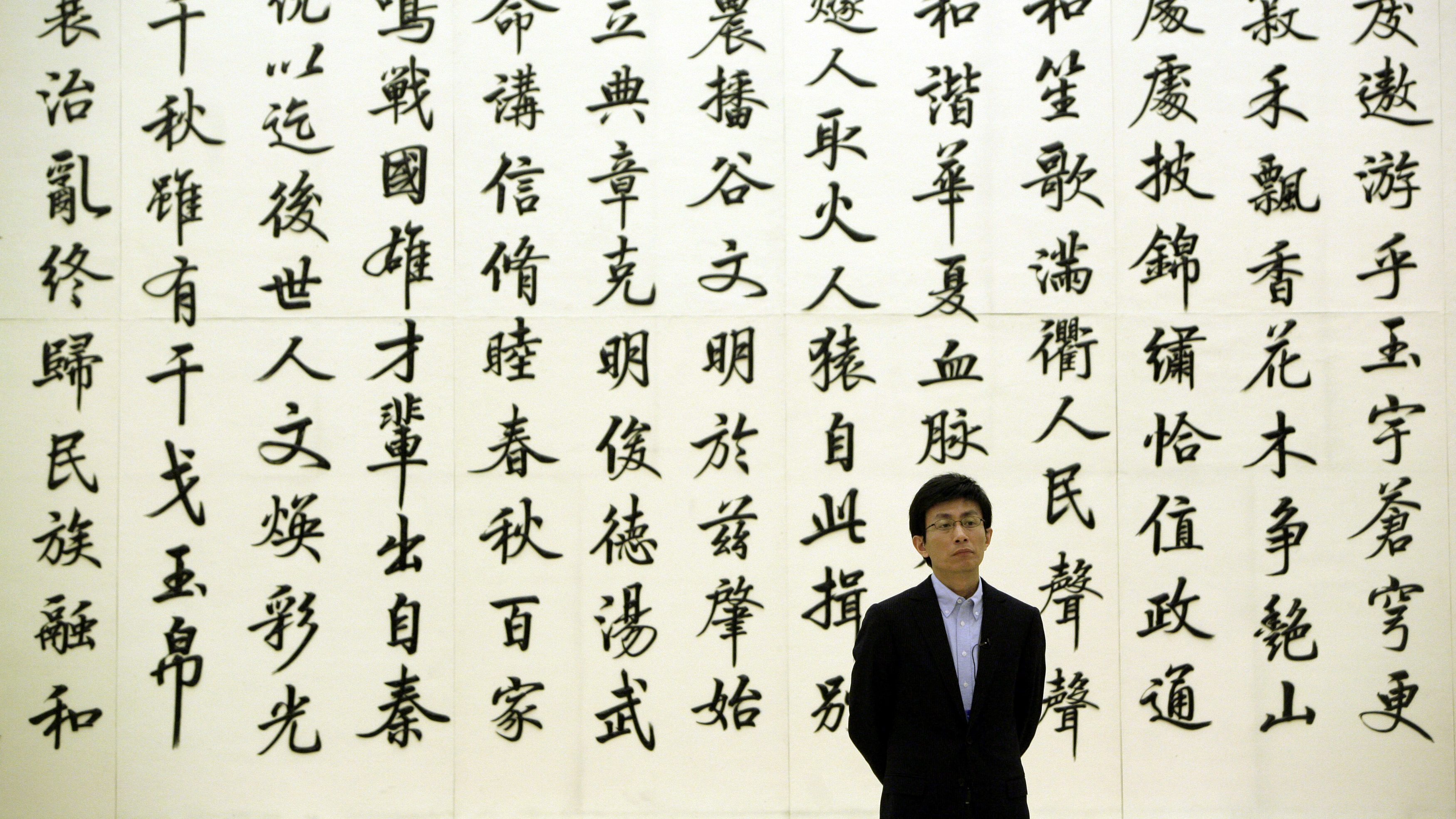 A man stands in front of a marble wall engraved with Chinese calligraphy poetry, in the Great Hall of the People, the venue of China's annual session of parliament, in Beijing March 6, 2010.