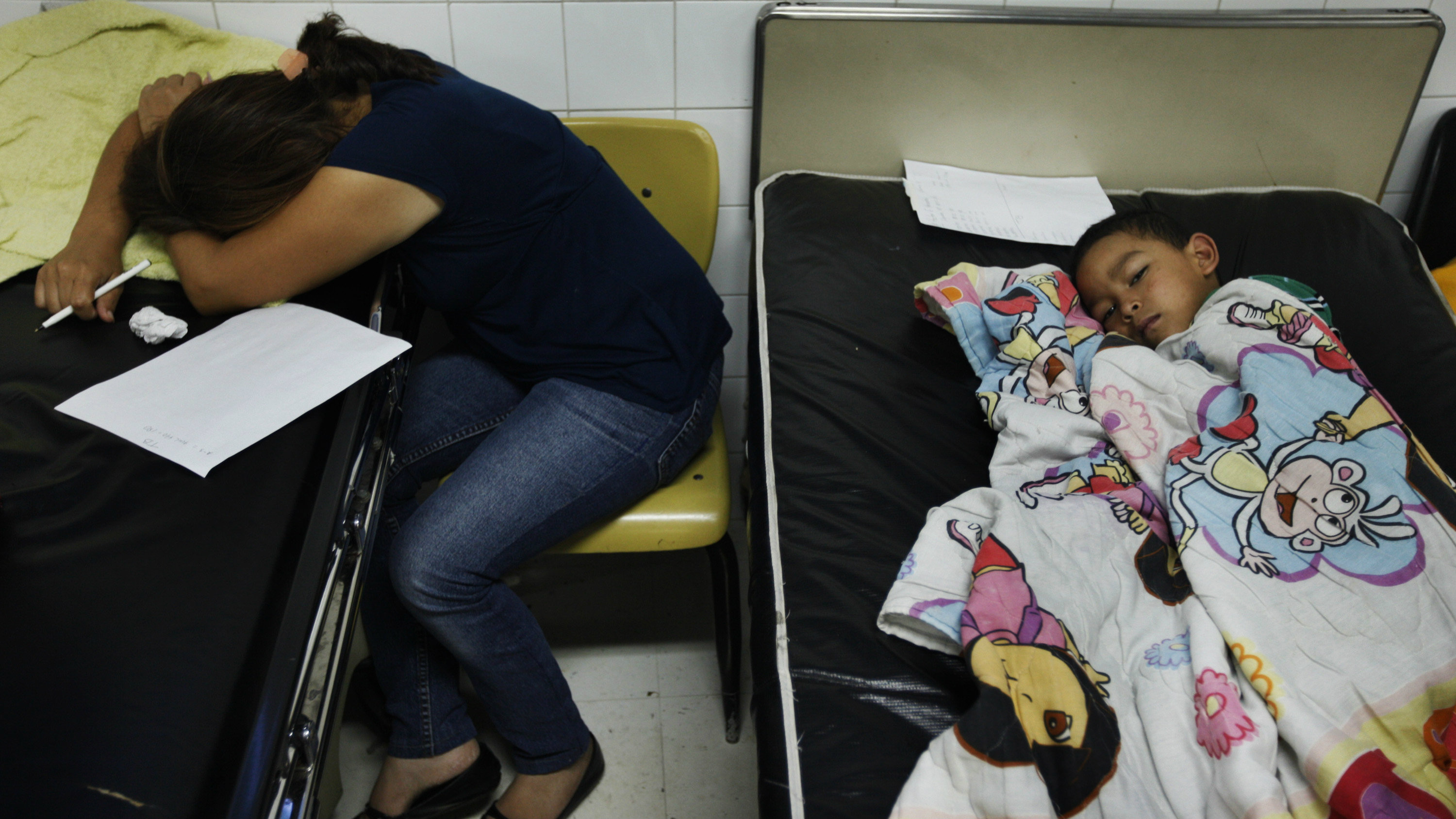 The mother of a patient suffering from dengue fever sleeps by his bedside at Hospital Escuela in Tegucigalpa..