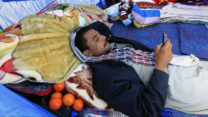 An Egyptian man who fled the unrest in Libya looks at his mobile phone while lying down at a UNHCR refugee camp near the Libyan and Tunisian border crossing of Ras Jdir March 1, 2011.