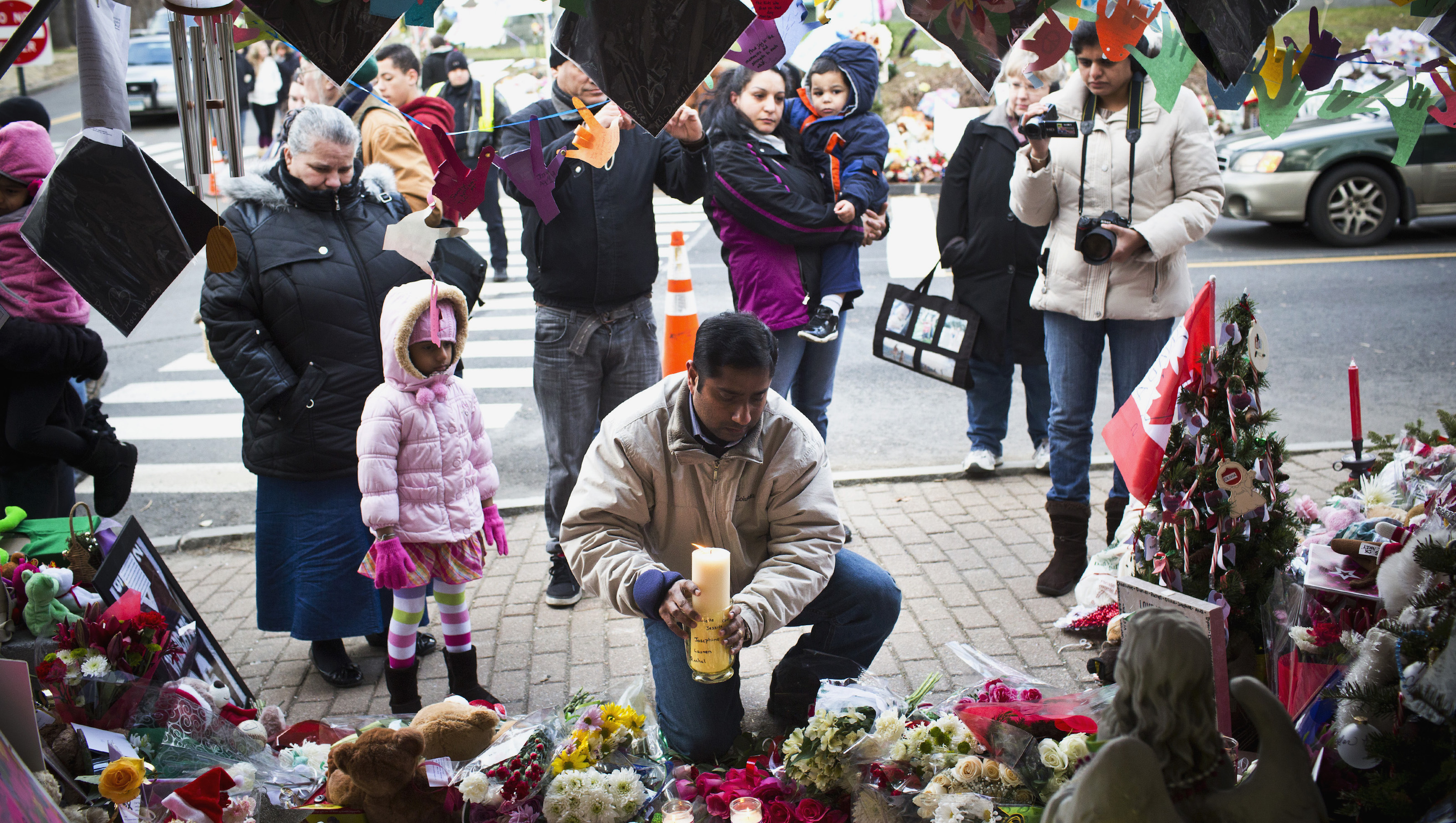 A man places a candle at a memorial for those killed in the massacre at Sandy Hook Elementary School in Sandy Hook, Connecticut December 22, 2012. REUTERS/Andrew Burton (UNITED STATES - Tags: CRIME LAW EDUCATION) - RTR3BUMN