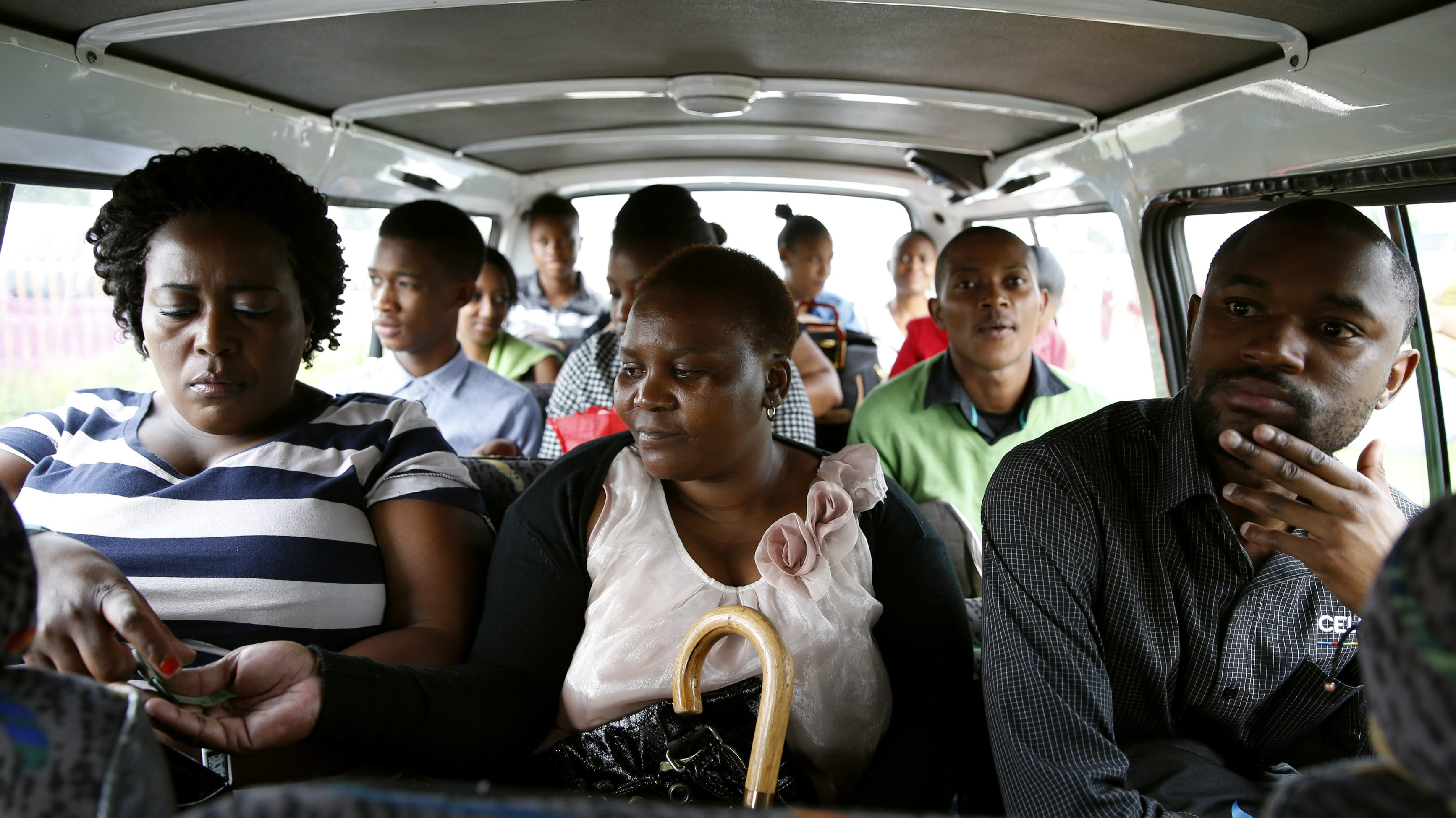 Passengers pass their fares to minibus taxi driver Zakes Hadebe as they commute from Soweto township to central Johannesburg February 21, 2014. South Africa's minibus taxi industry, scorned by other motorists for reckless driving and dogged by a reputation for violence, moves 15 million people every day, most of them lower income blacks. More like buses than the taxis of New York or London, the rumbling 16-seaters are the wheels of Africa's largest economy. Picture taken February 21. To match story SAFRICA-TAXIS/ REUTERS/MIke Hutchings (SOUTH AFRICA - Tags: TRANSPORT BUSINESS EMPLOYMENT) - RTR3GEZN