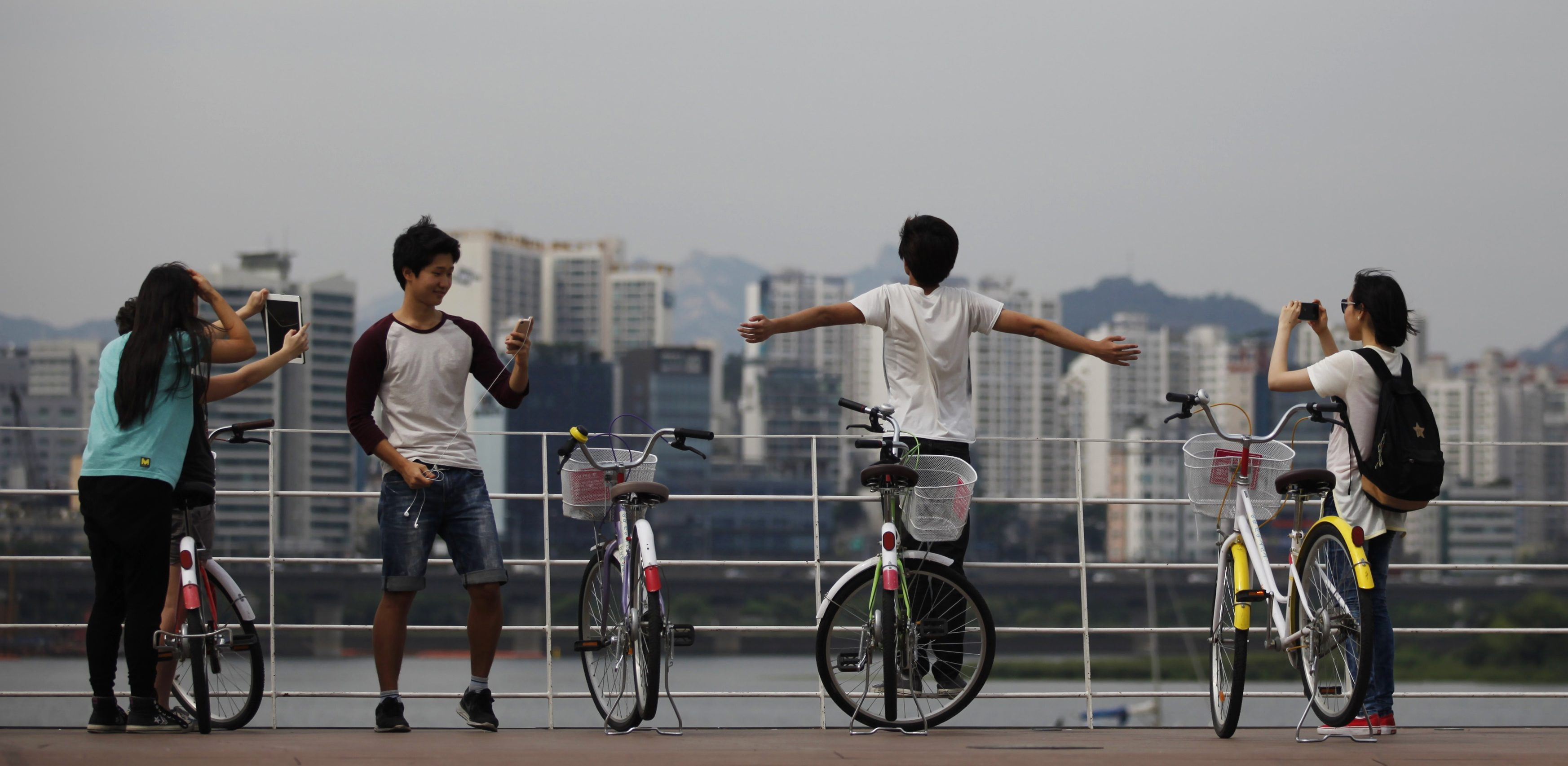 Youths take photographs with their smart devices at the Han River park in Seoul June 16, 2014.