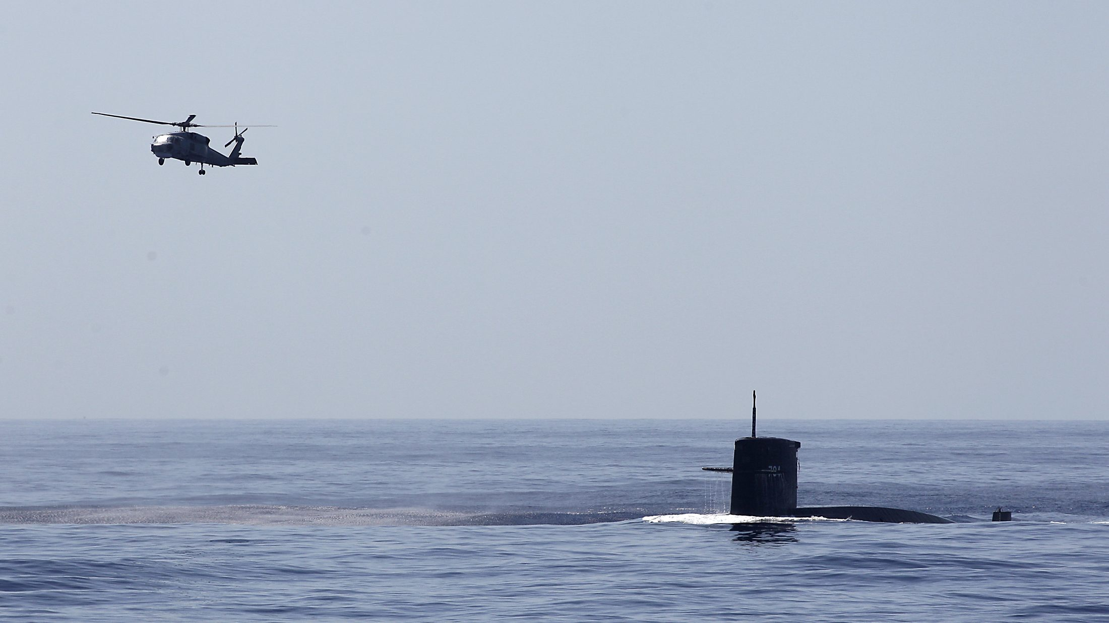 An S-70C helicopter flies over a submarine during the Han Kuang military exercise held about 10 nautical miles eastern of the port of Hualien, eastern Taiwan, September 17, 2014