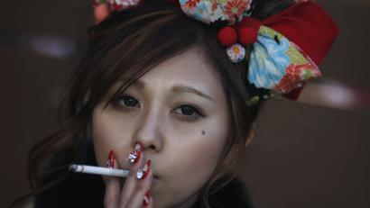 Juri Mitomi, 20, holds a cigarette after a Coming of Age Day celebration ceremony at an amusement park in Tokyo January 12, 2015.