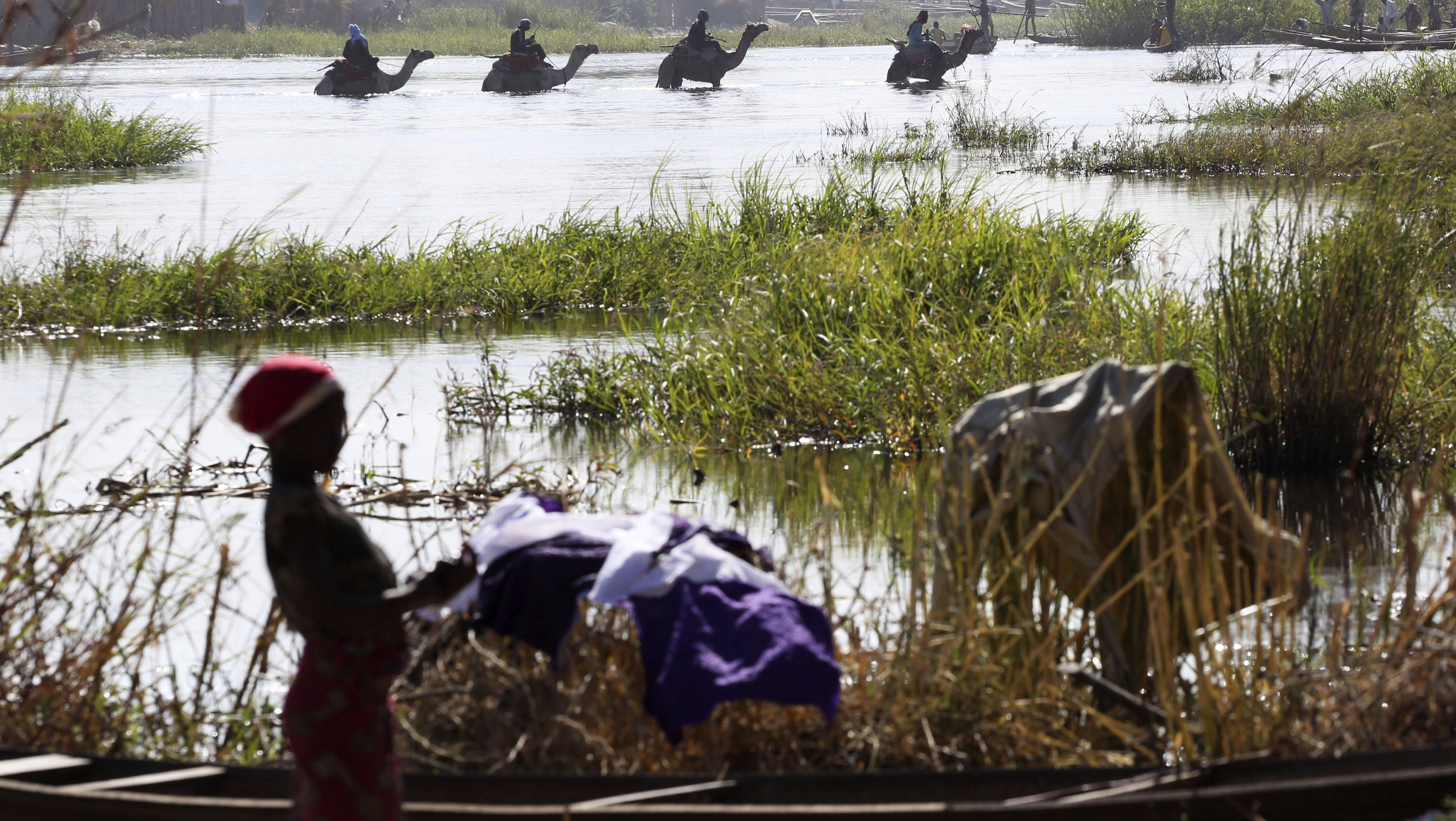 Men on camels cross the water as a woman washes clothes in Lake Chad in Ngouboua