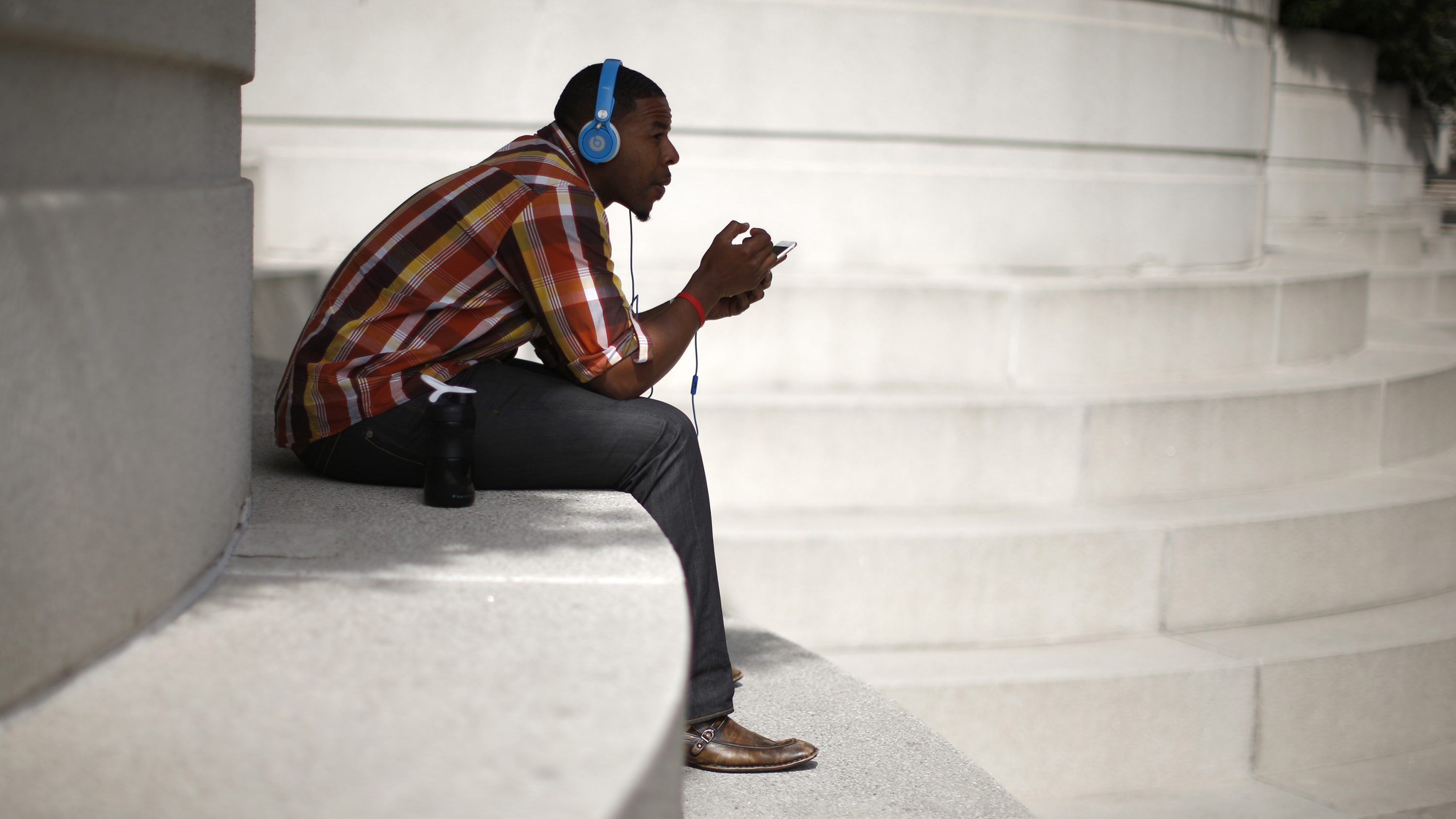 A man with Beats headphones listens to music on an iPhone in Los Angeles, California March 10, 2015.
