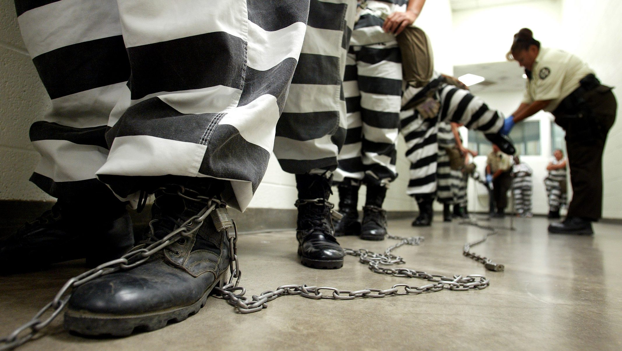 Maricopa County female inmates are padlocked by the ankle for chain gang duty in Phoenix, Arizona October 21, 2003. The women are padlocked together by the ankle and marched military style to a van to be transported to their work site. The women volunteer for chain gang duty to get out of lockdown, where four prisoners are shut in a cell 8 x 12 feet wide 23 hours day. If they spend 30 days on the chain gang, picking up trash, weeding or burying bodies, they can get out of the punishment cell.  Pictures of the month October 2003. REUTERS/Shannon Stapleton PP03100138  SS - RTR5Y7H