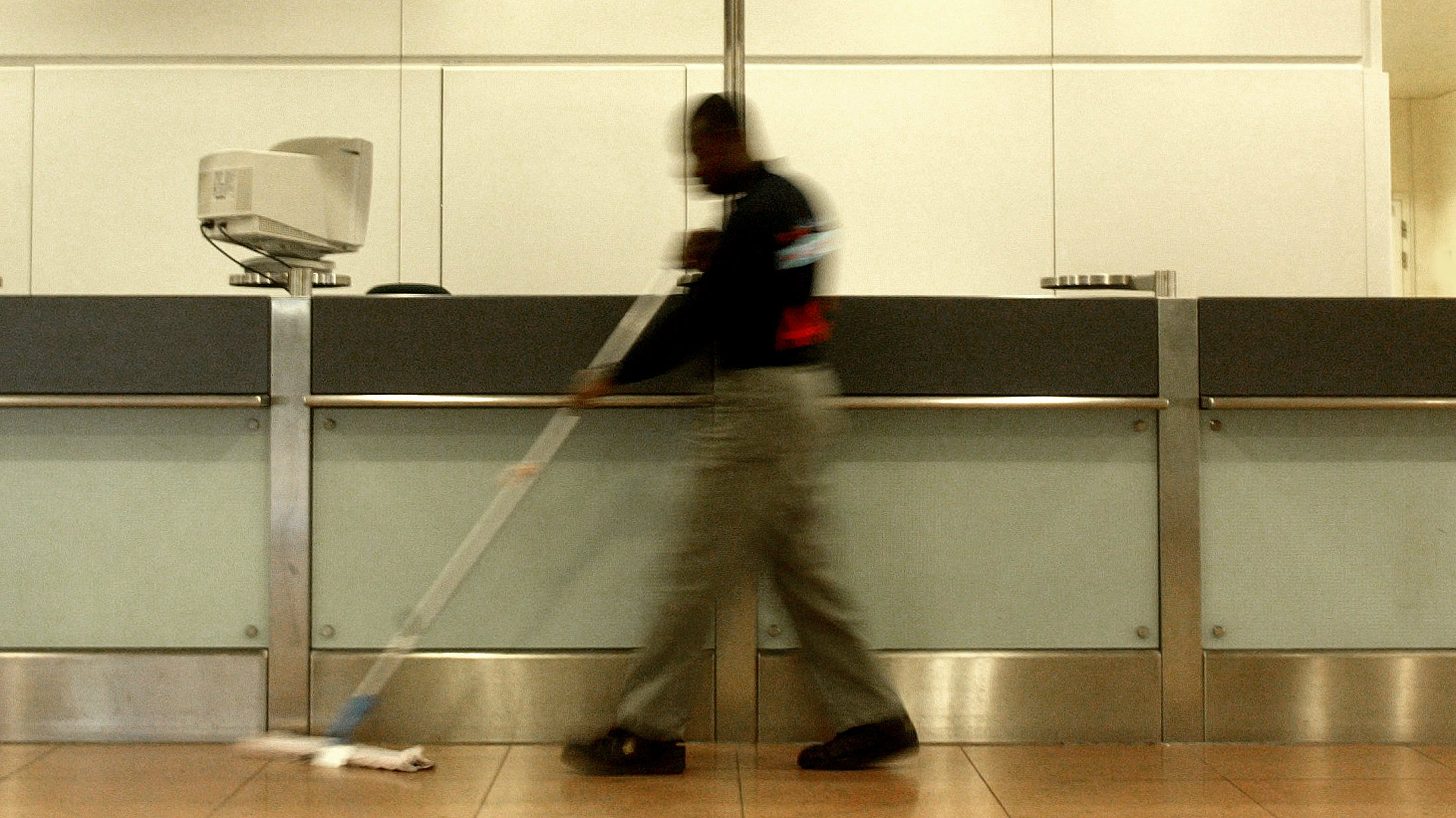 A janitor sweeps up at an airport.