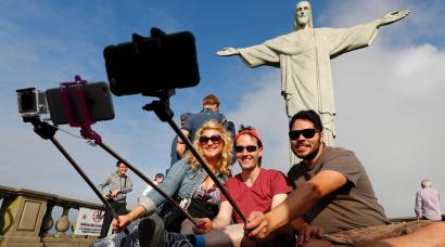 Tourists pose for selfies in front of Christ the Redeemer.