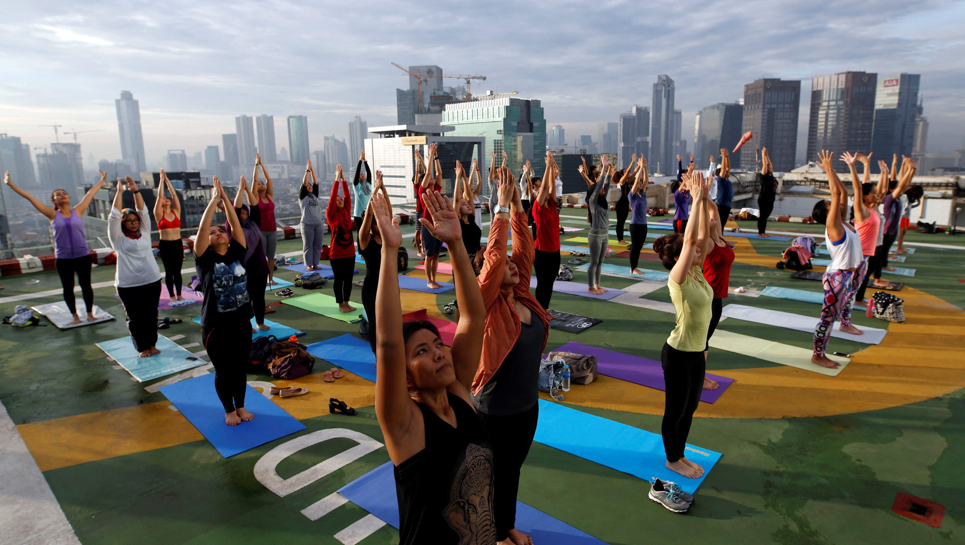 People take part in a sunrise yoga class on the helicopter landing pad on the roof of the Grand Sahid Jaya hotel in Jakarta, Indonesia September 25, 2016.REUTERS/Darren Whiteside - RTSPAX1