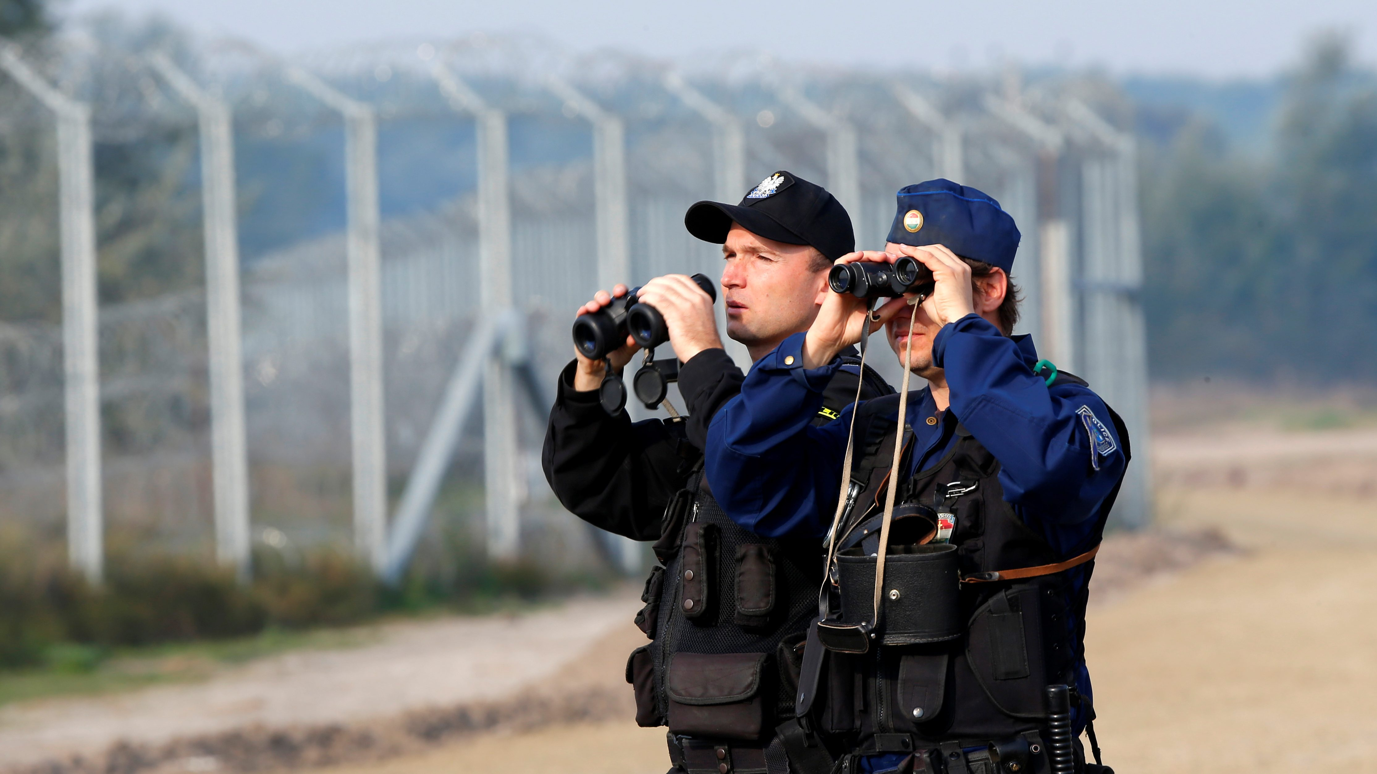 Hungarian and Polish policeman patrol at the Hungary-Serbia border fence near the village of Asotthalom