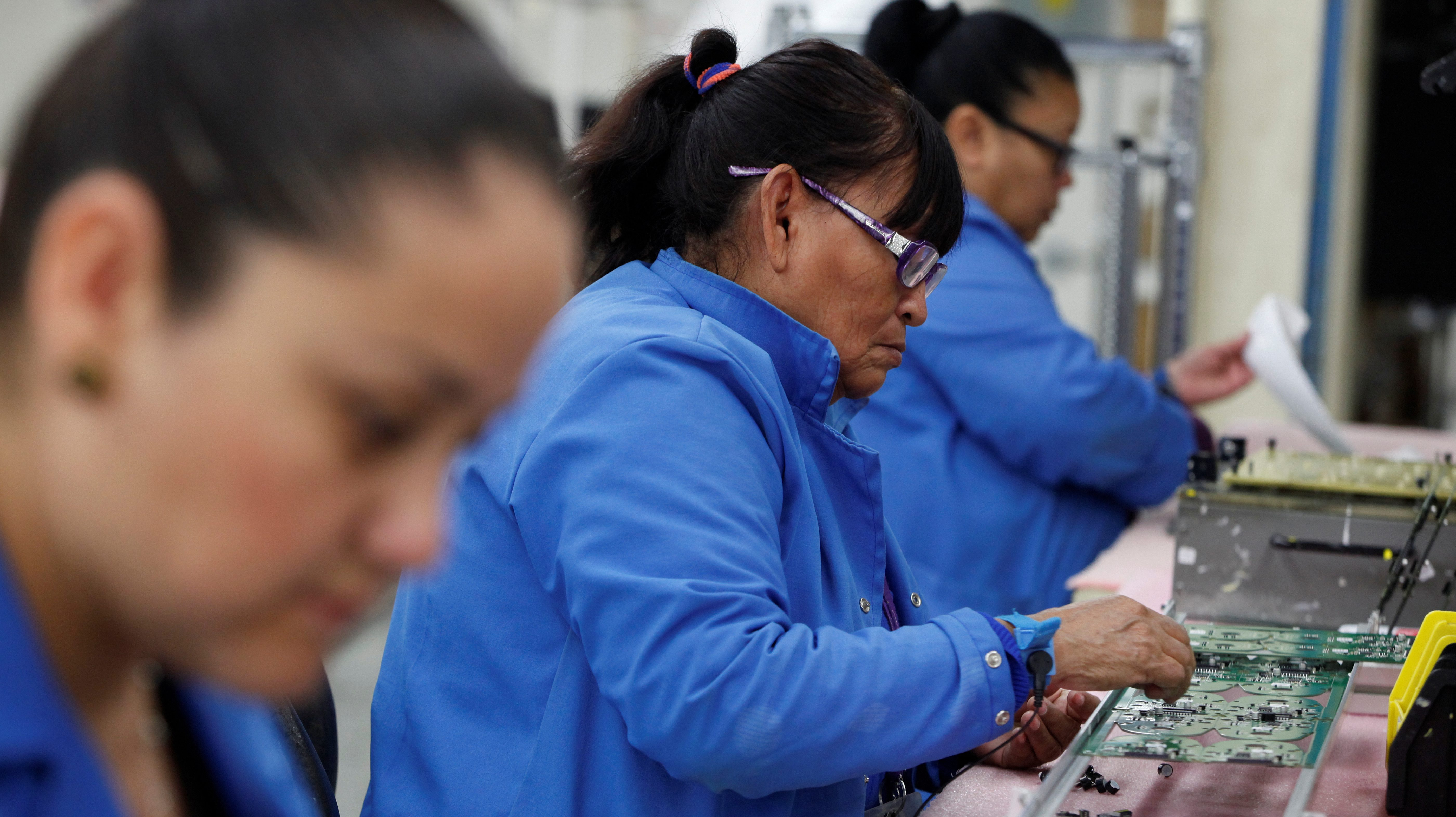 Employees work on a printed circuit board at the assembly line of a factory that exports to the U.S. in Ciudad Juarez, Mexico