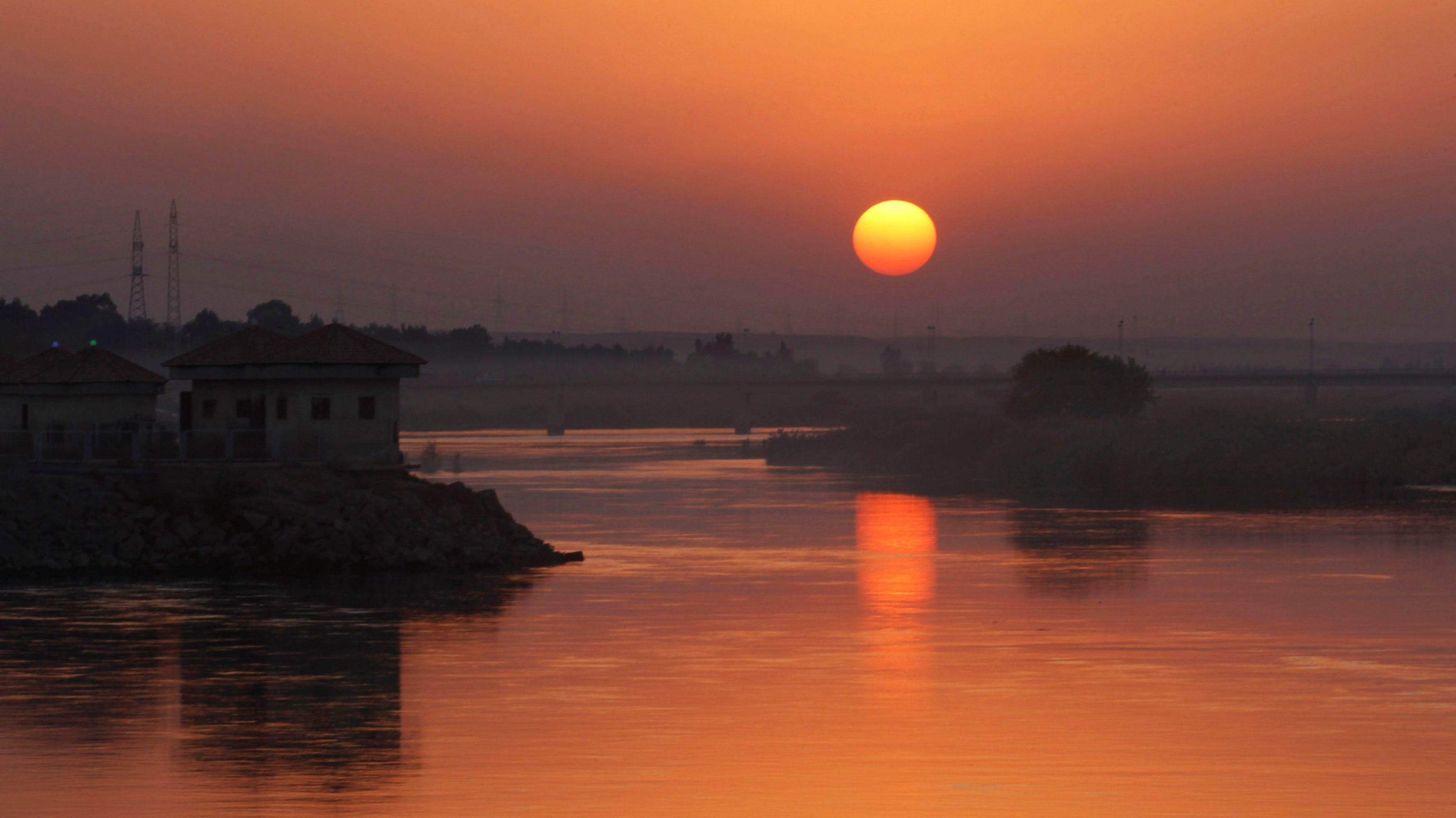 The sun sets over the Euphrates river in Raqqa.