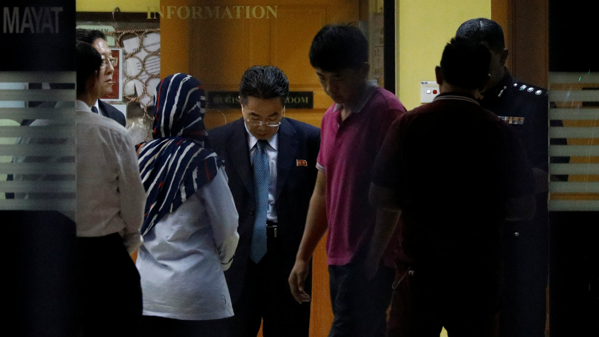 A North Korea official speaks with officials at the morgue in Kuala Lumpur where Kim Jong-nam's body is being held.
