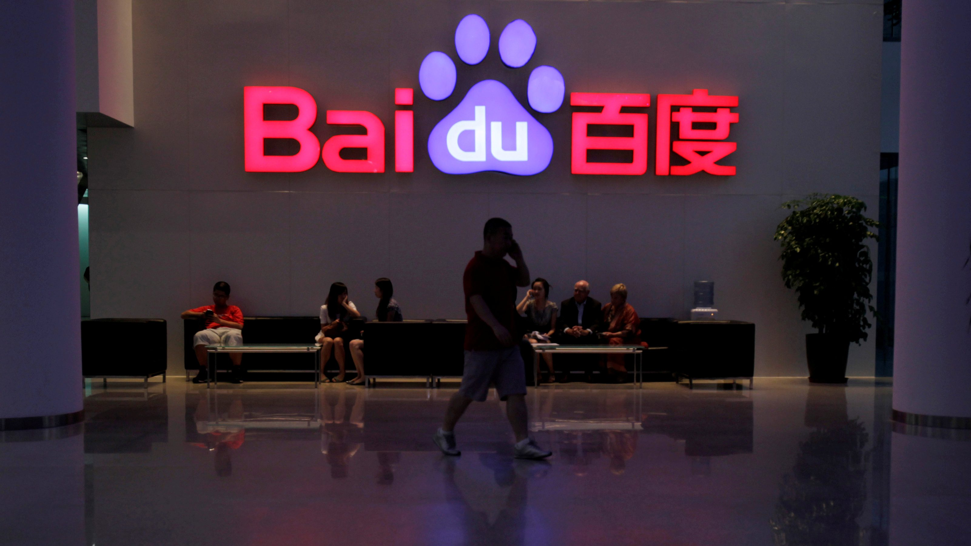 FILE PHOTO -  A employee uses his mobile phone as he walks past the company logo of Baidu at its headquarters in Beijing, August 5, 2010. REUTERS/Barry Huang/File Photo                    GLOBAL BUSINESS WEEK AHEAD   SEARCH GLOBAL BUSINESS 20 FEB FOR ALL IMAGES - RTSZFE3