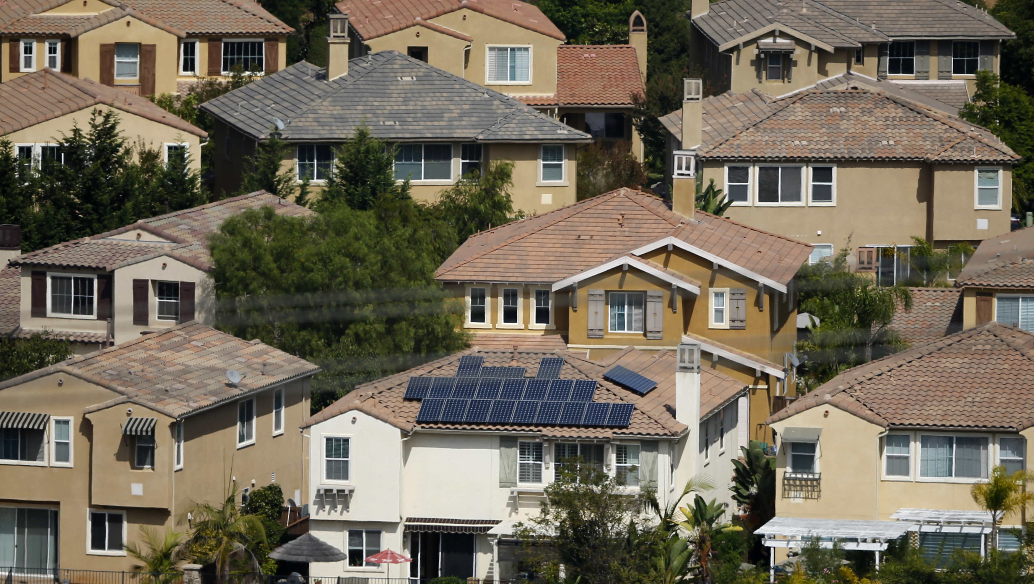 A home with solar panels on its roof is shown in a residential neighborhood in San Marcos, California September 19,2013. Well over 60 percent of solar systems in states like California and Arizona today are owned by a third party and financed, allowing homeowners to go solar by paying a monthly fee for panels instead of shouldering the $20,000 to $30,000 up front cost of a system. Photo taken September 19, 2013.