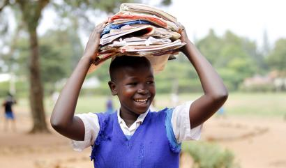 A student carries books at the Senator Obama primary school near ancestral home of U.S. President Barack Obama in Nyangoma village in Kogelo, west of Kenya's capital Nairobi, June 23, 2015. When Barack Obama visits Africa this month, he will be welcomed by a continent that had expected closer attention from a man they claim as their son, a sentiment felt acutely in the Kenyan village where the 44th U.S. president's father is buried. Picture taken June 23, 2015.