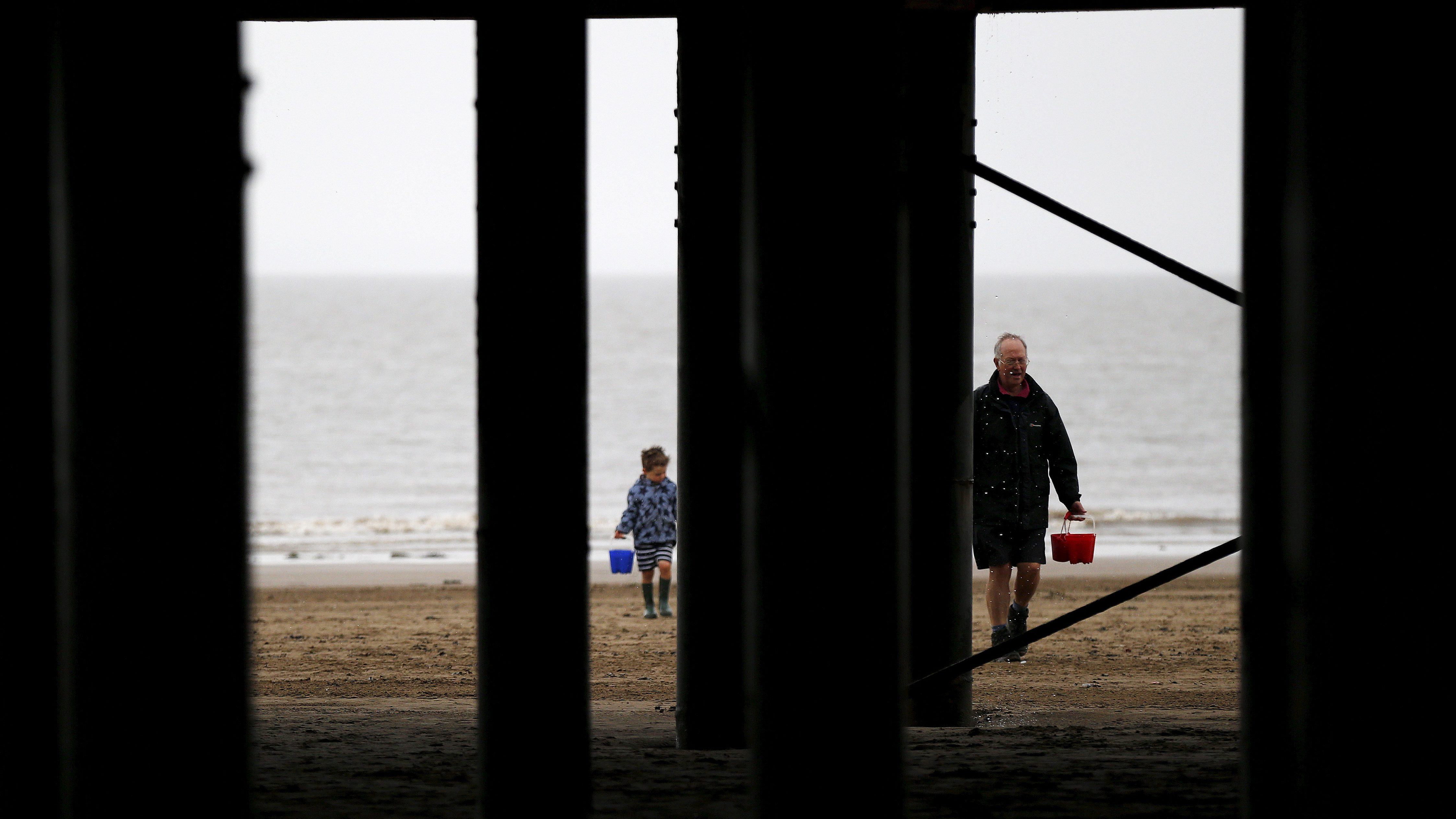 A man and a boy carry buckets of water to make sand castles underneath a boardwalk on the seaside in Weston-super-Mare