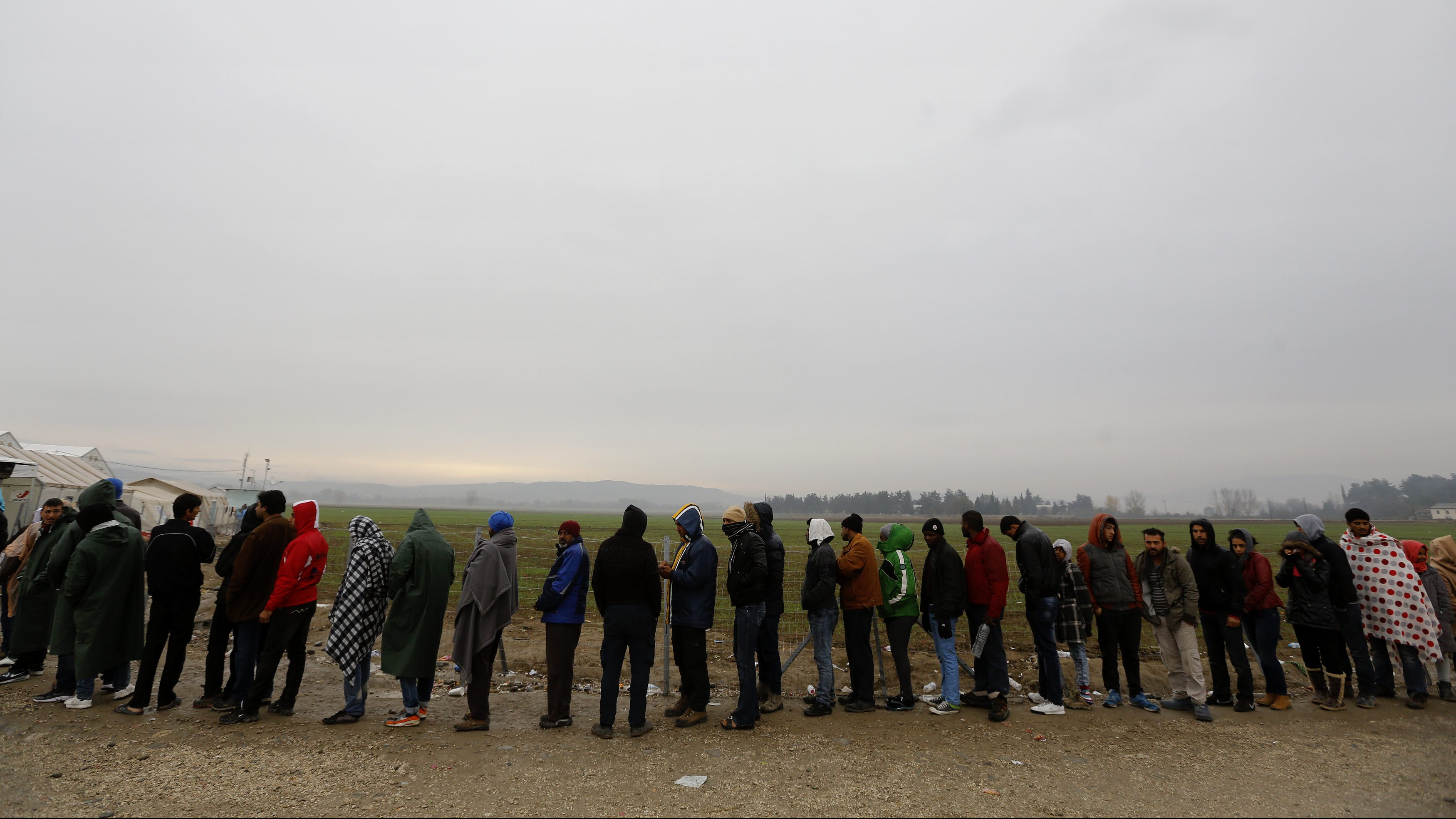 Hundreds of stranded migrants line up during food distribution at the Greek-Macedonian border near the Greek village of Idomeni