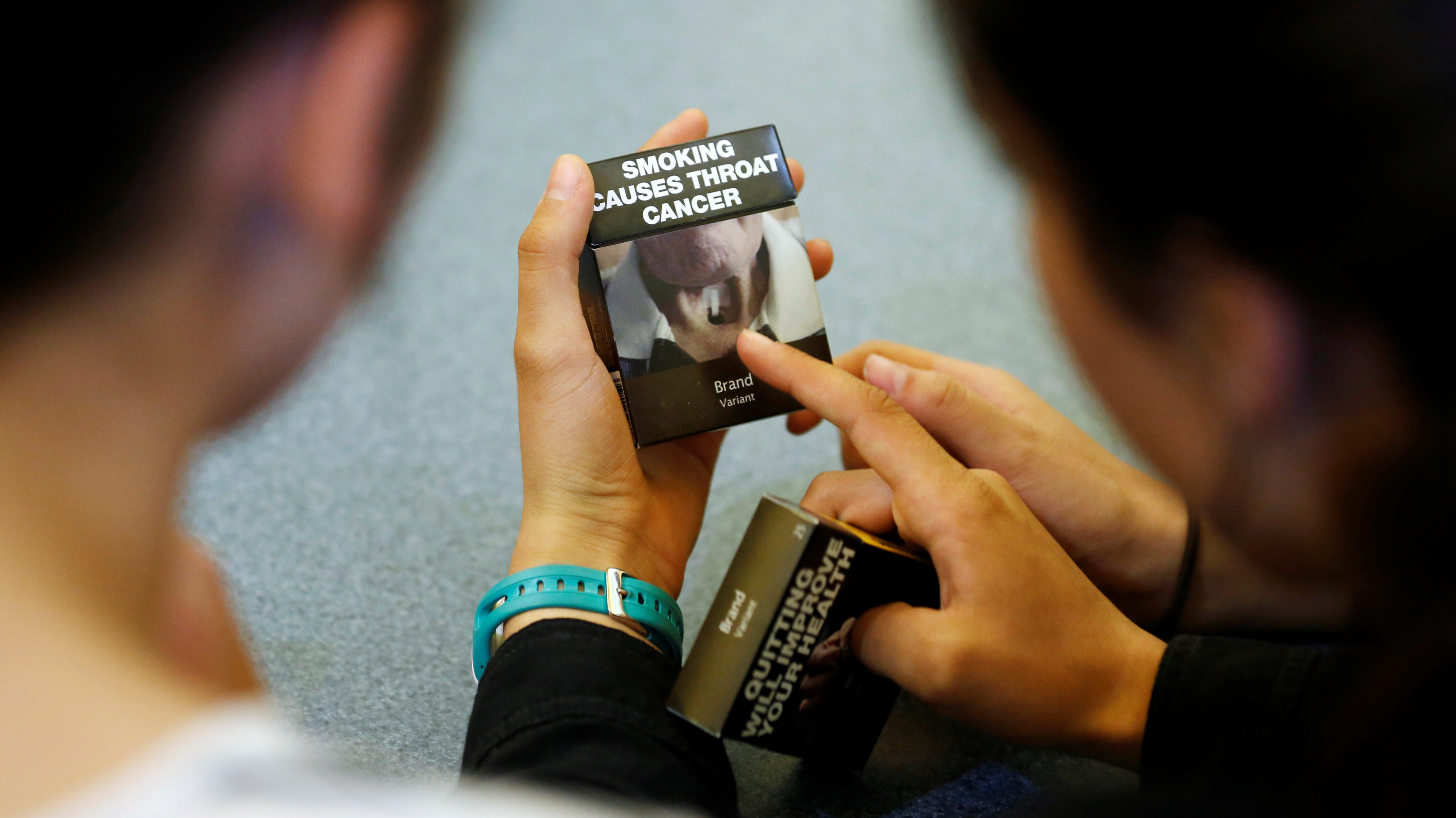 High school students look at a mock up of plain cigarette packaging in Ottawa