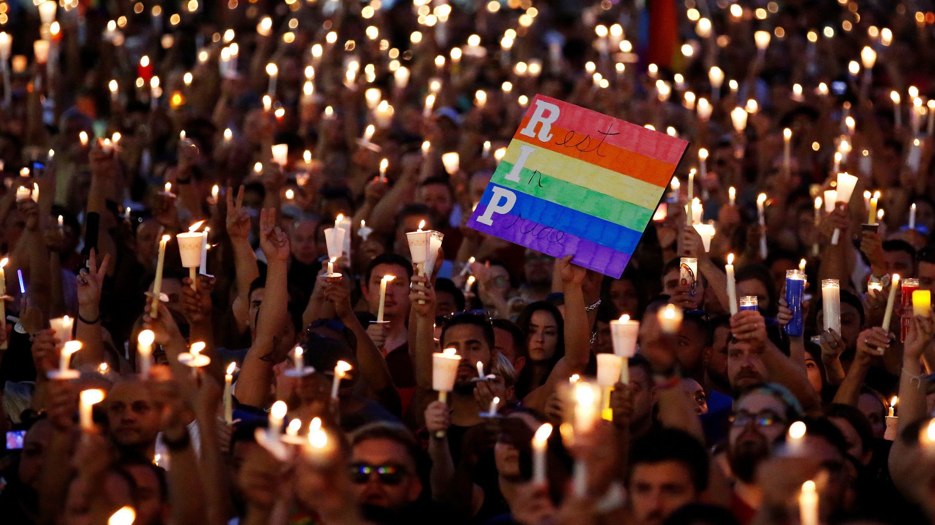 People take part in a candlelight memorial service the day after a mass shooting at the Pulse gay nightclub in Orlando, Florida, U.S. June 13, 2016.