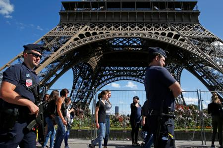 French CRS policemen patrol as tourists walk past in front of the Eiffel Tower in Paris, France August 20, 2016.