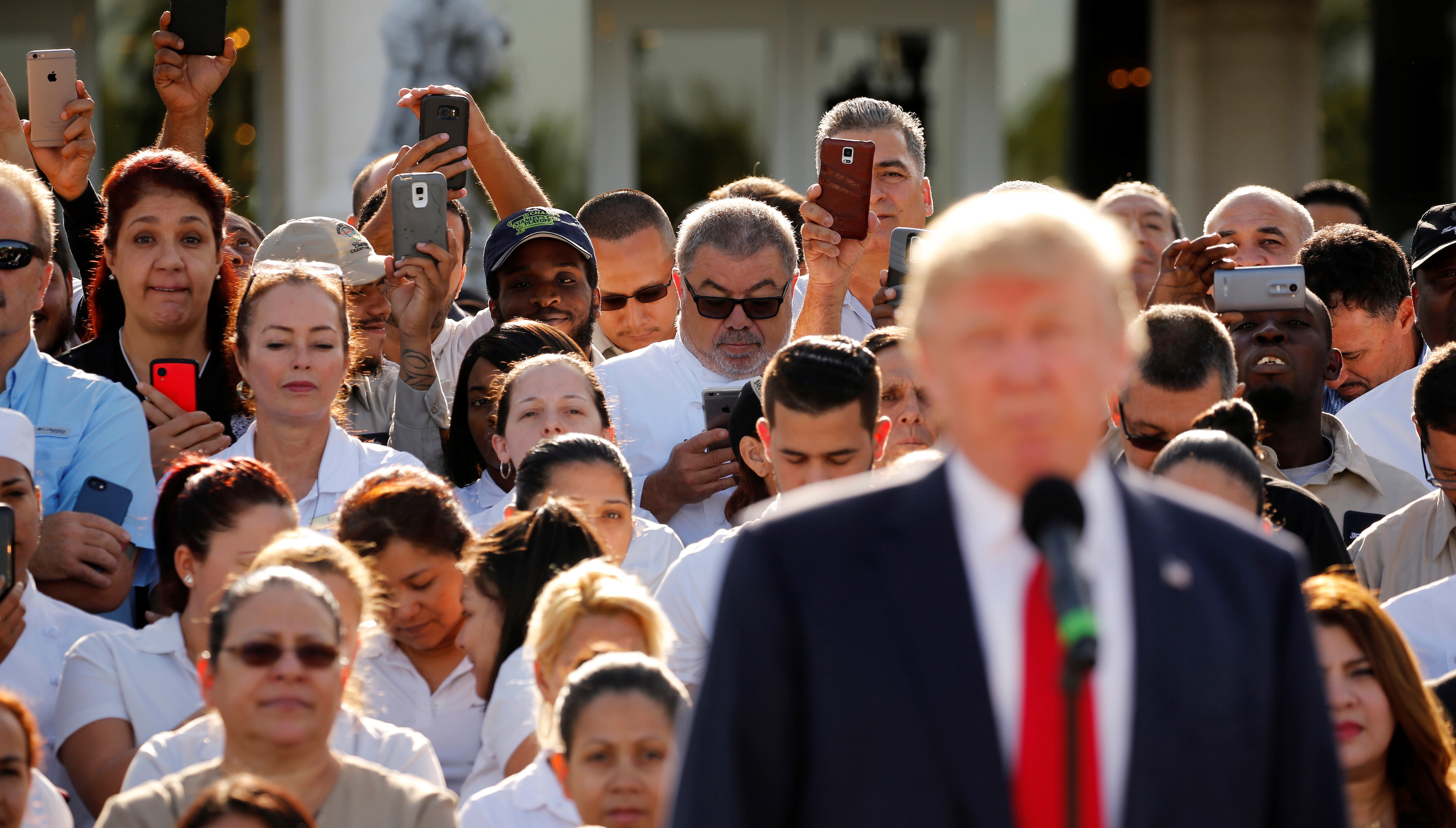 Employees of Republican U.S. presidential nominee Donald Trump stand behind him in support at a campaign event at his Trump National Doral golf club in Miami, Florida, U.S. October 25, 2016. REUTERS/Jonathan Ernst - RTX2QDWN