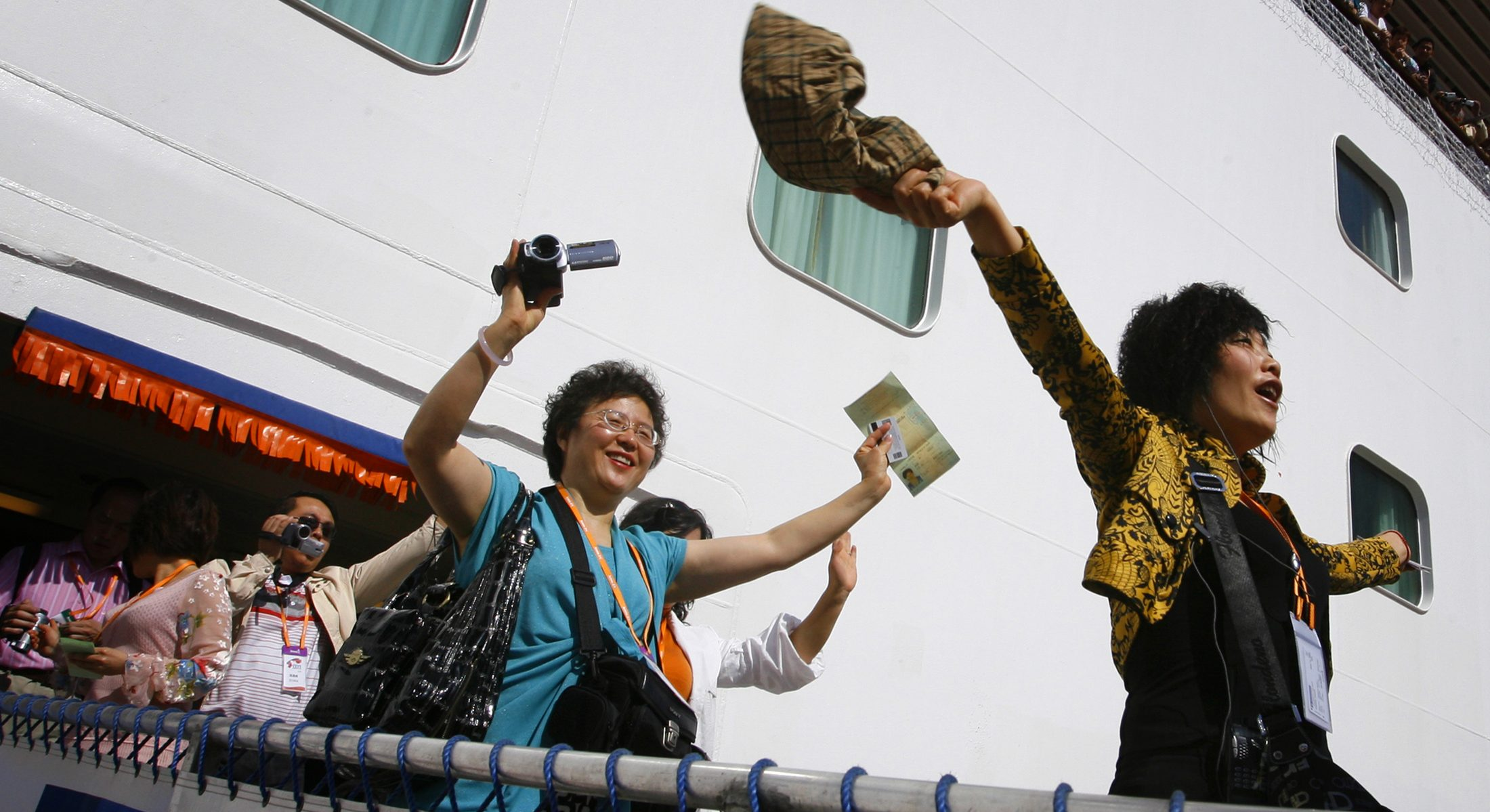 Tourists from China wave as they arrive on a cruise ship in the northern Taiwan port of Keelung, March 16, 2009.