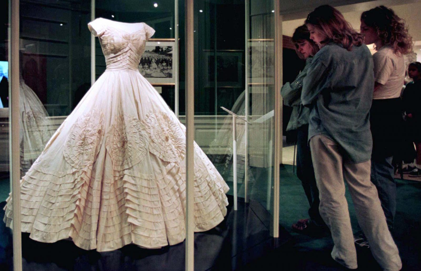 Visitors to the John F. Kennedy Library Museum admire Jacqueline Bouvier Kenndey's wedding dress in Boston, May 27.  John F. Kennedy Jr. and his sister Caroline donated the dress to the museum after their mother's death.  The dress is made of over 50 yards of ivory silk taffeta. - RTXHHRH