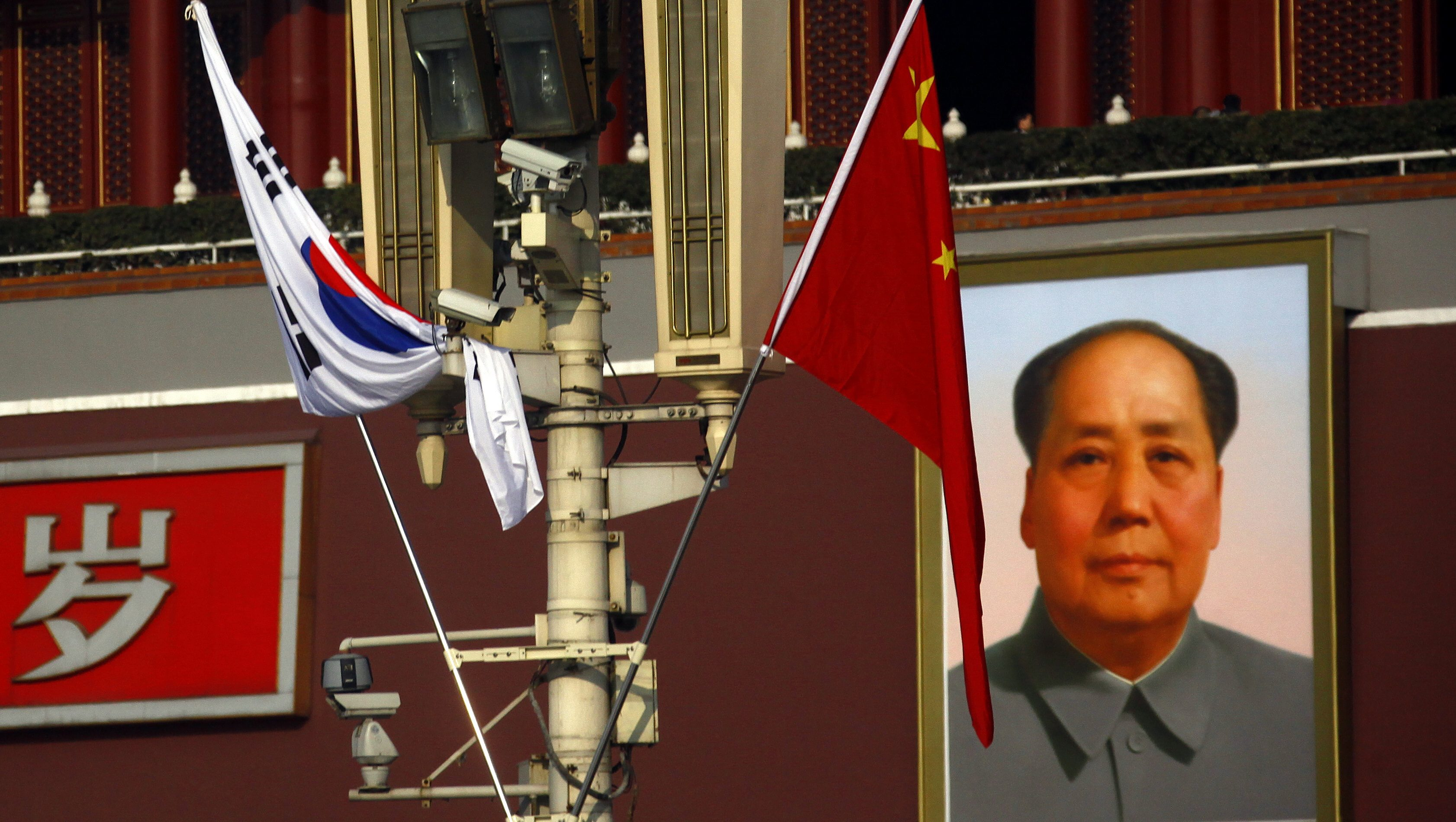 South Korean and Chinese national flags hang from a pole in front of the giant portrait of former Chinese chairman Mao Zedong at Beijing's Tiananmen Square January 9, 2012. South Korean President Lee Myung-bak is on a three-day trip to China, his second in four years, and will ask China's leaders to use their influence to lean on North Korea to show restraint amid a delicate transition to a new leadership.