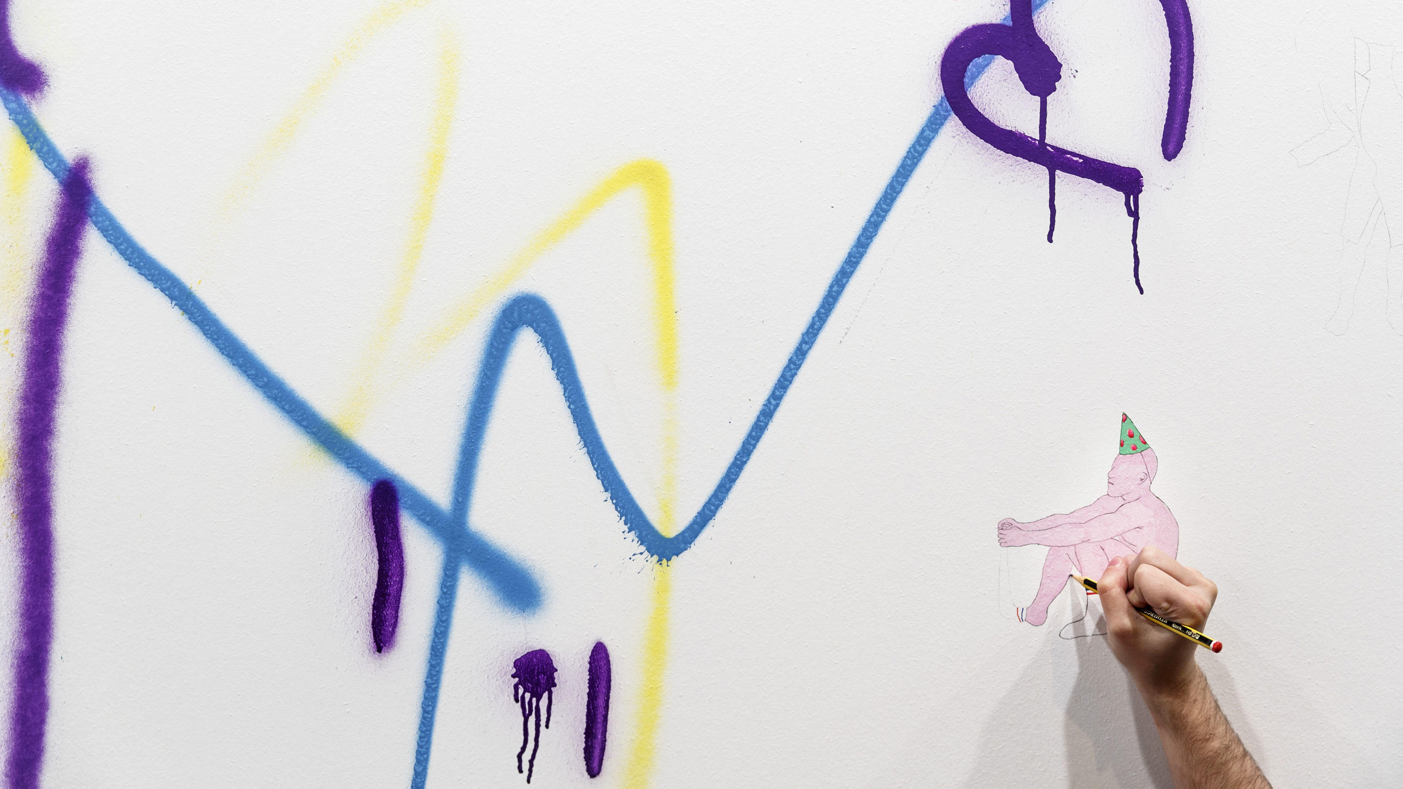 a hand draws a figure on a wall