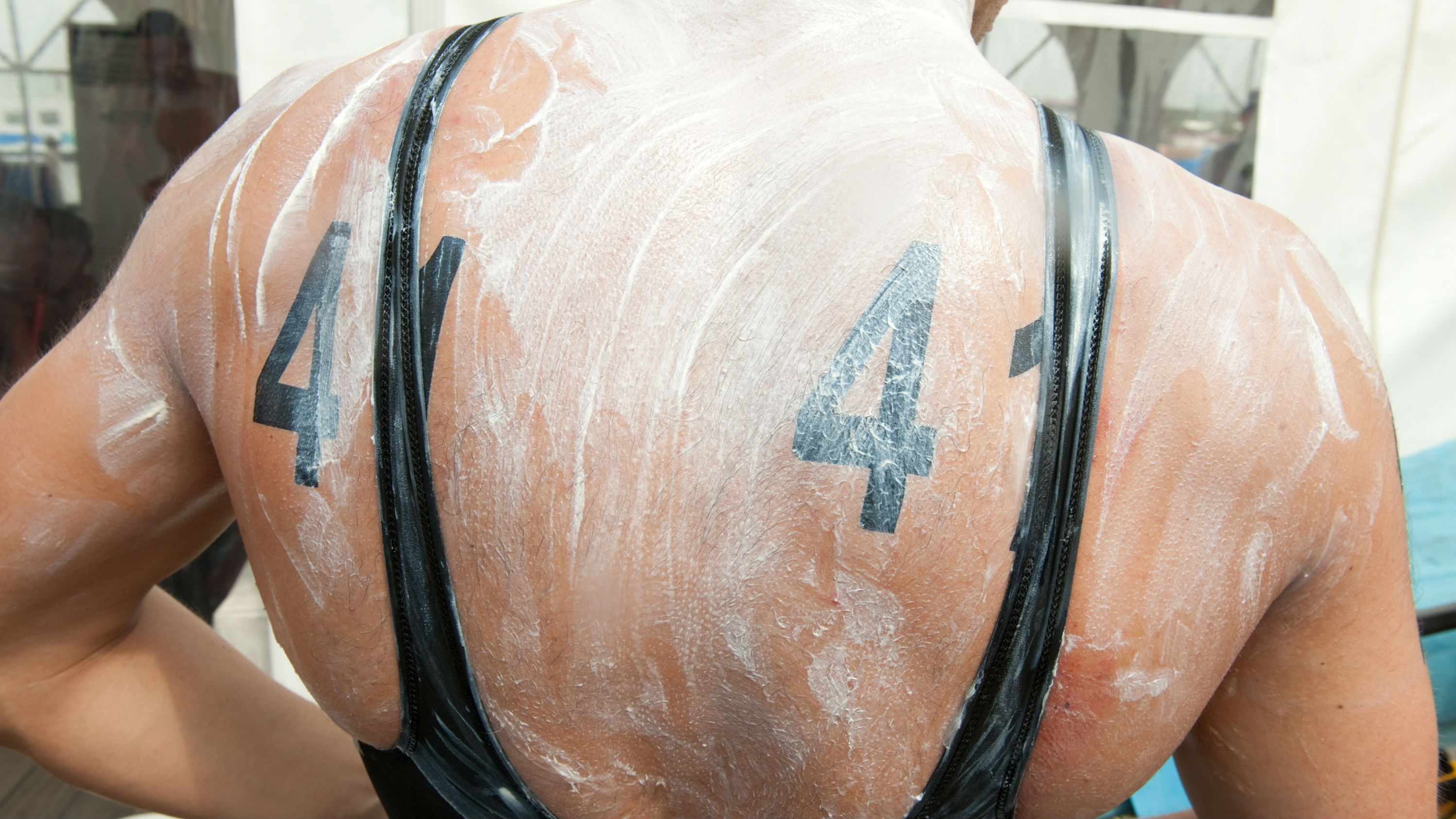 A triathlete's back covered in white sunscreen.