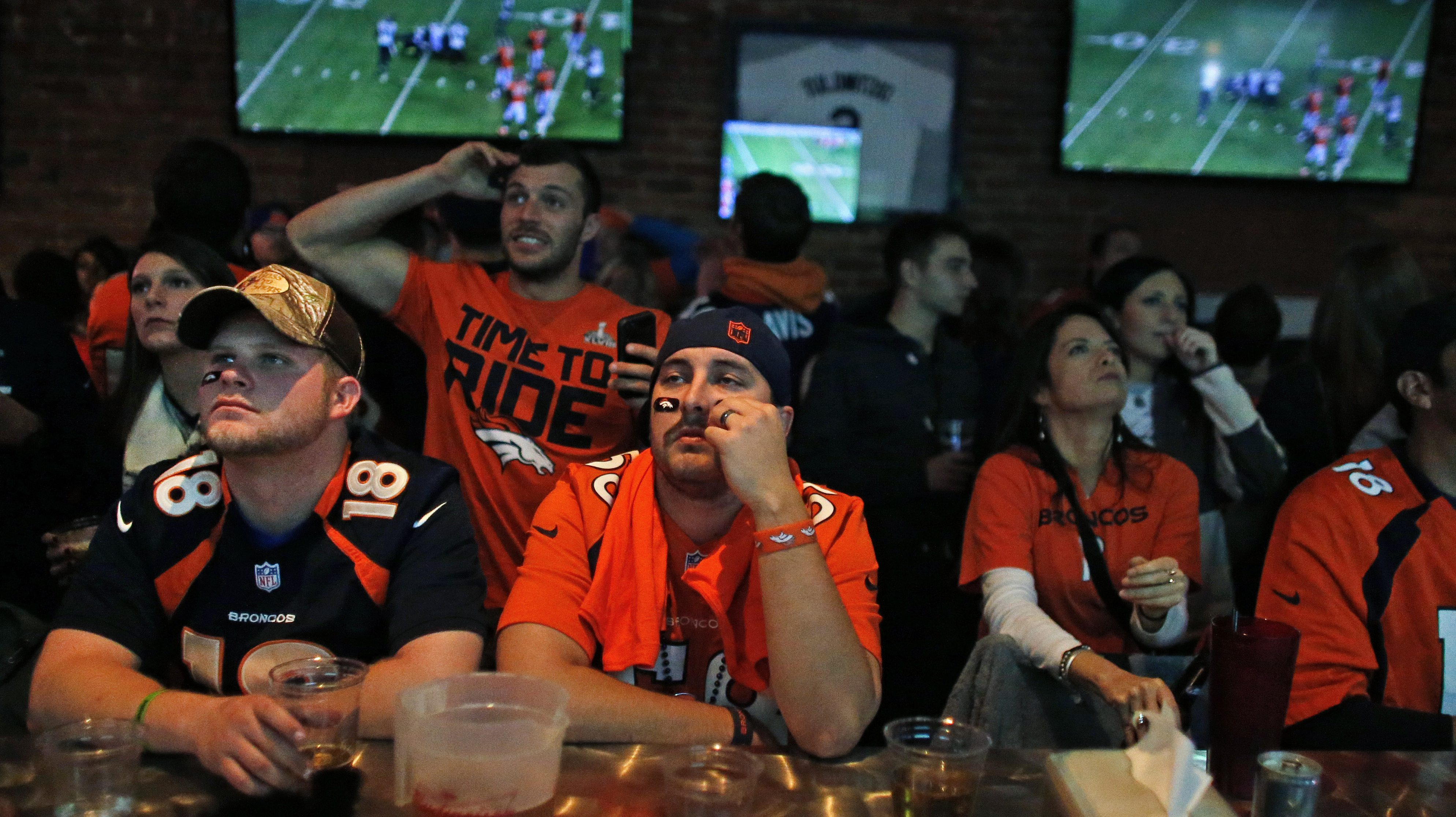 """FILE - In this Feb. 2, 2014 file photo, Denver Broncos fans watch their team play the Seahawks during the first half of the Super Bowl, inside Jackson's, a sports bar and grill in Denver. Senators from both parties warned the National Football League Thursday to get rid of a 4-decade-old TV """"blackout"""" rule or risk congressional action to restrict the league's lucrative antitrust exemption, which allows NFL teams to negotiate radio and television broadcast rights together.  (AP Photo/Brennan Linsley, File)"""