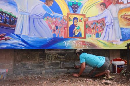 A drug surrenderer works on a mural at the Baclaran as part of the church's livelihood program to support victims of the drug war.