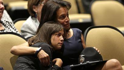 Susan Oliver, the wife of slain Sacramento County Deputy Danny Oliver, comforts their daughter, Jenny