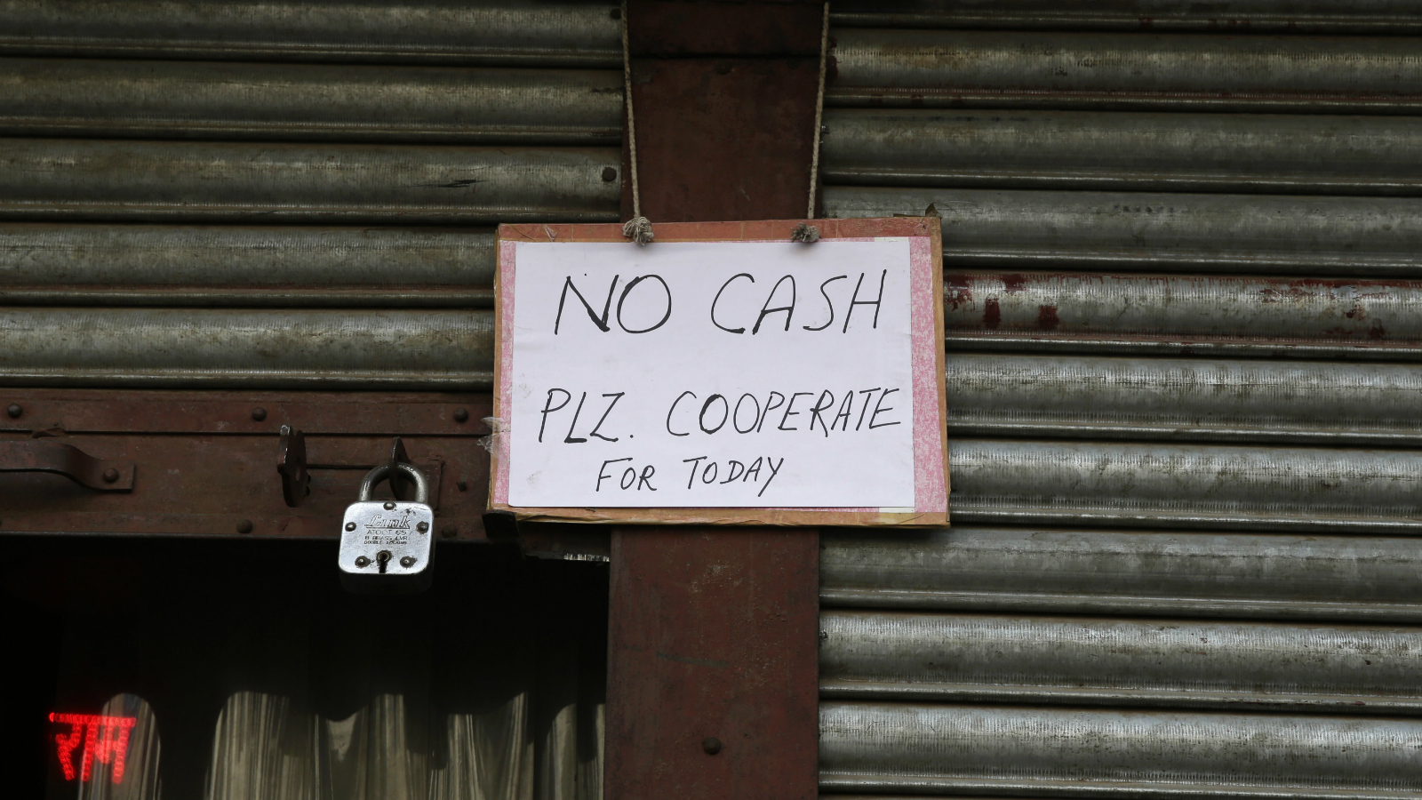 A notice is hung outside a bank as it ran out of cash in Delhi, India, Thursday, Dec. 1, 2016. Indian Prime Minister Narendra Modi, in his Nov. 8 televised address, announced demonetization of India's 500 and 1,000-rupee notes, which made up 86 percent of the country's currency. People have been forced to stand in long queues to change banned notes and also to take out new currency from their accounts after severe limitations were imposed on withdrawal from banks and ATMs.