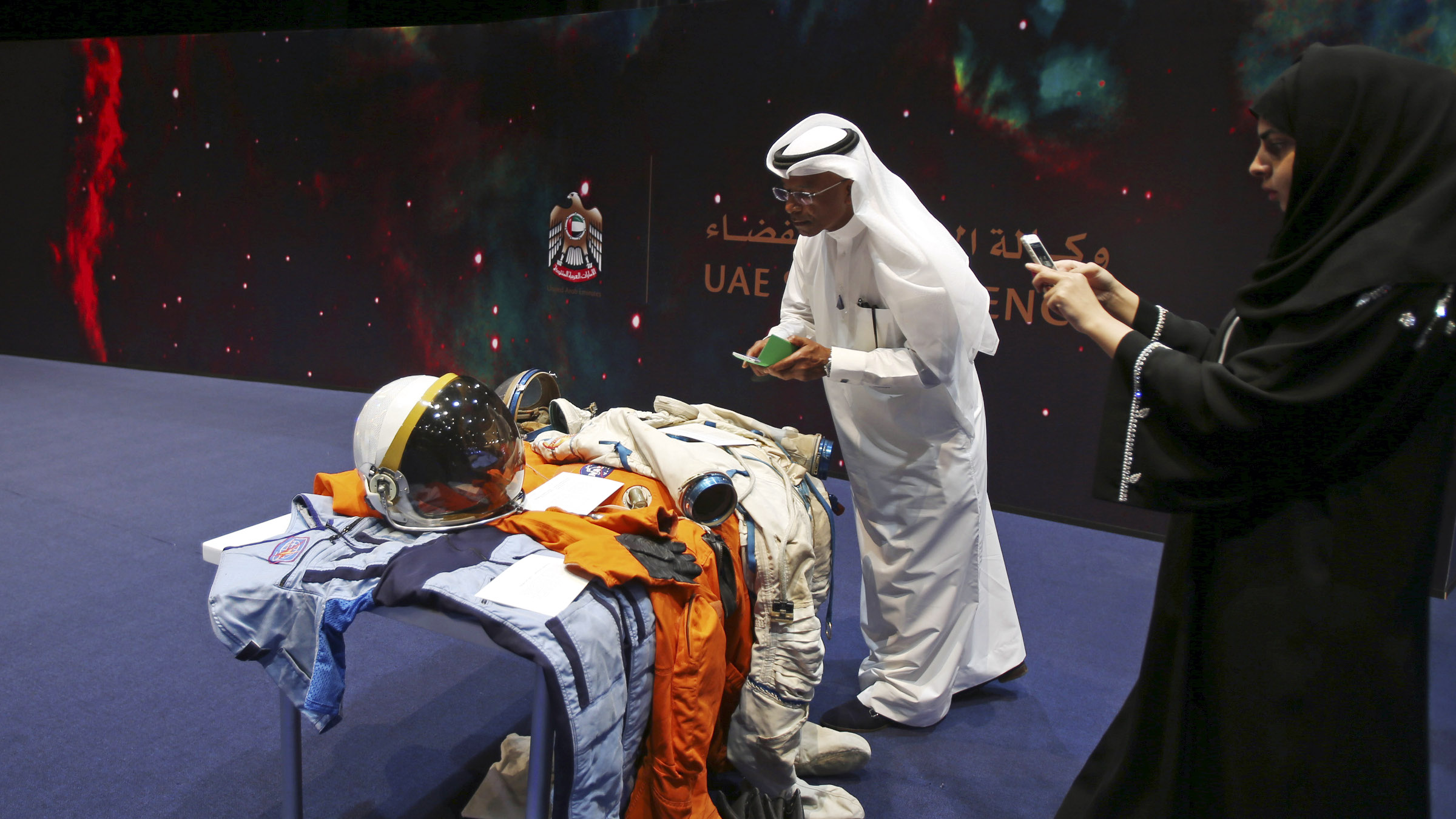Emirati visitors take photos at the Space Museum during the launch of the UAE Space Agency strategic plan in Abu Dhabi, United Arab Emirates, Monday, May 25, 2015. The agency on Monday laid out a strategic framework for a newly created space agency that aims to integrate various arms of the Gulf federation's burgeoning space industry. The announcement comes less than three weeks after the Dubai-based team behind a 2020 mission to Mars announced that its probe will circle the planet studying its atmosphere, including changes over time and how surface features such as volcanoes, deserts and canyons affect it. (