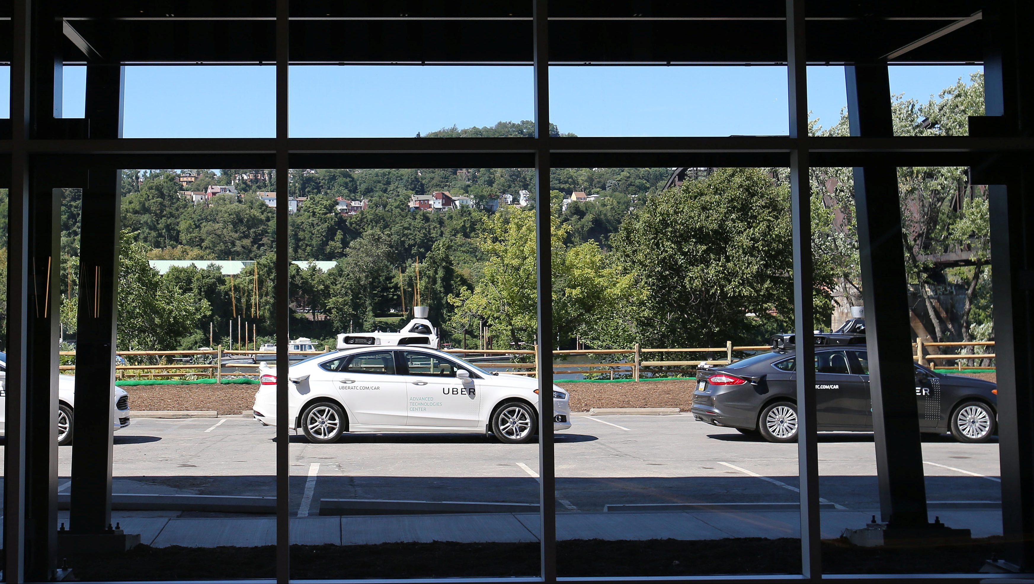 A fleet of Uber's Ford Fusion self driving cars are shown through the lobby windows during a demonstration of self-driving automotive technology in Pittsburgh, Pennsylvania, U.S. September 13, 2016.  REUTERS/Aaron Josefczyk - RTSNO61