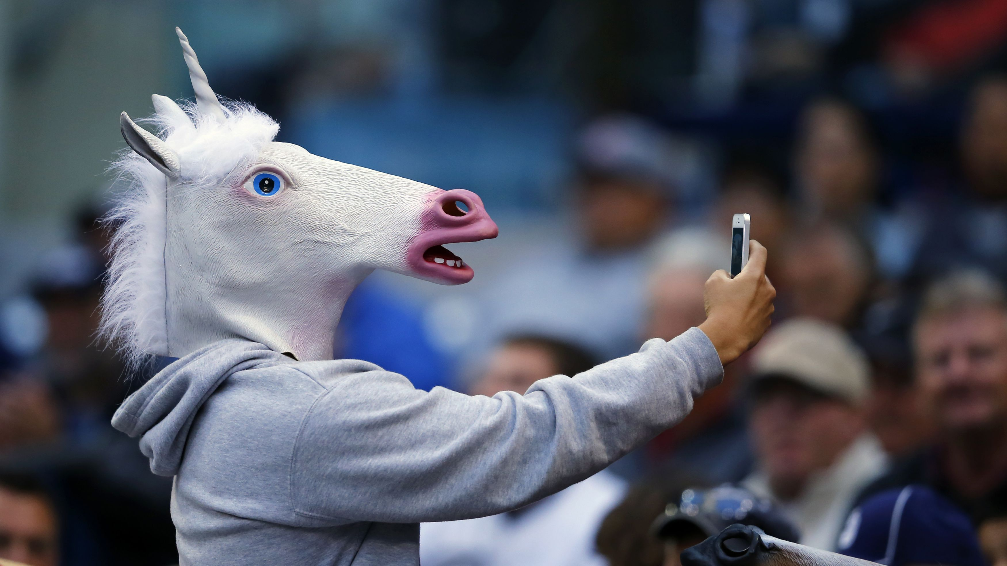 A baseball fan wearing a unicorn mask takes a picture of himself with his phone as he attends the Interleague MLB game between the San Diego Padres and the Toronto Blue Jays in San Diego, California June 2, 2013. REUTERS/Mike Blake (UNITED STATES - Tags: SPORT BASEBALL SOCIETY)