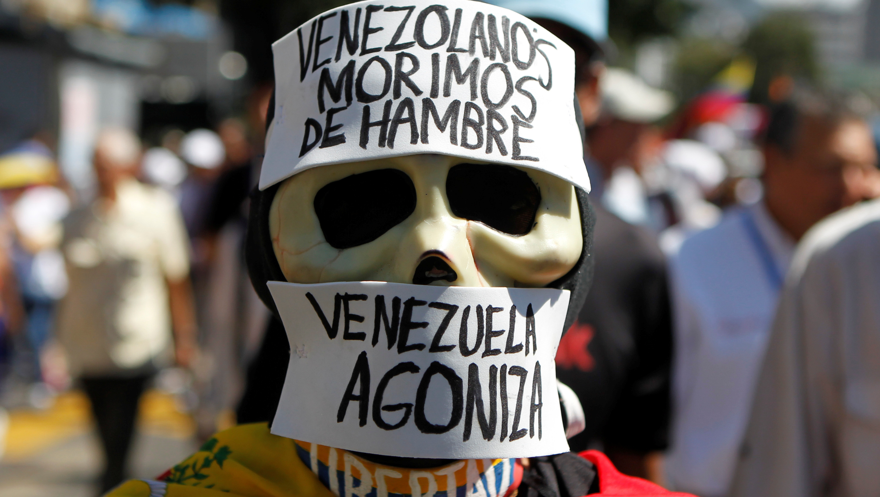 A man dressed in opposition to President Maduro of Venezuela wears a sign that says Venezuelans are starving.