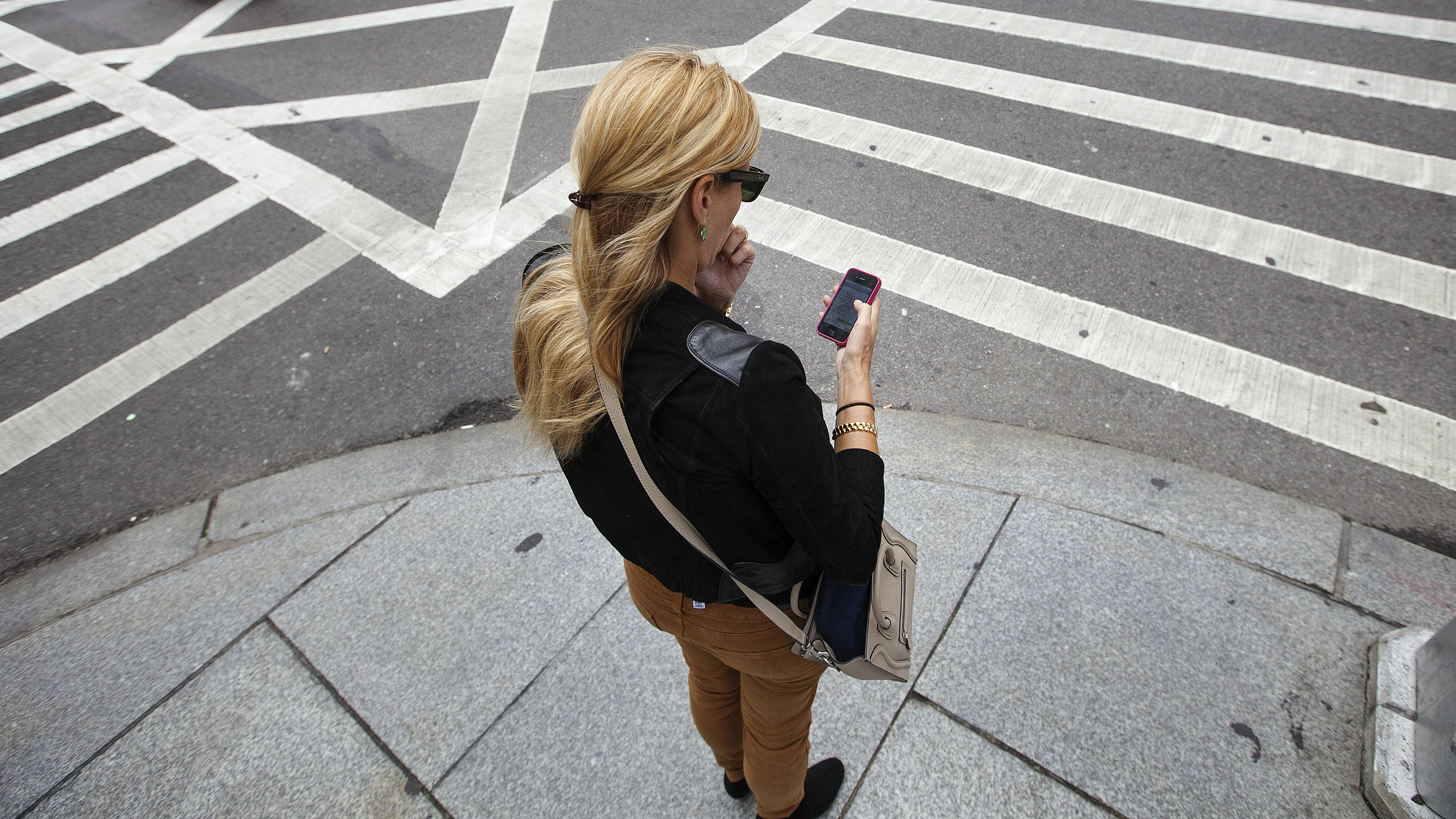 A woman uses her Apple iPhone while waiting to cross 5th Avenue in New York, September 20, 2012. Apple's iPhone 5 goes on sale tomorrow as Apple works to increase it's market share in the mobile phone market. REUTERS/Lucas Jackson (UNITED STATES - Tags: BUSINESS SCIENCE TECHNOLOGY TELECOMS SOCIETY)