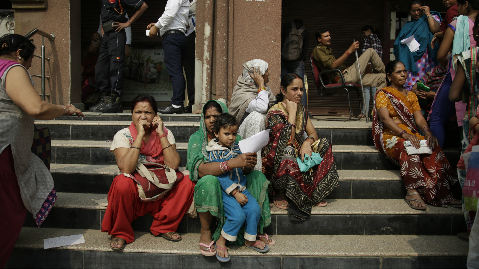 Indian women take rest on the stairs as others wait in a queue to deposit and exchange discontinued currency notes outside a bank on the outskirts of New Delhi, India, Friday, Nov. 11, 2016. Delivering one of India's biggest-ever economic upsets, Prime Minister Narendra Modi this week declared the bulk of Indian currency notes no longer held any value and told anyone holding those bills to take them to banks to deposit or exchange them.