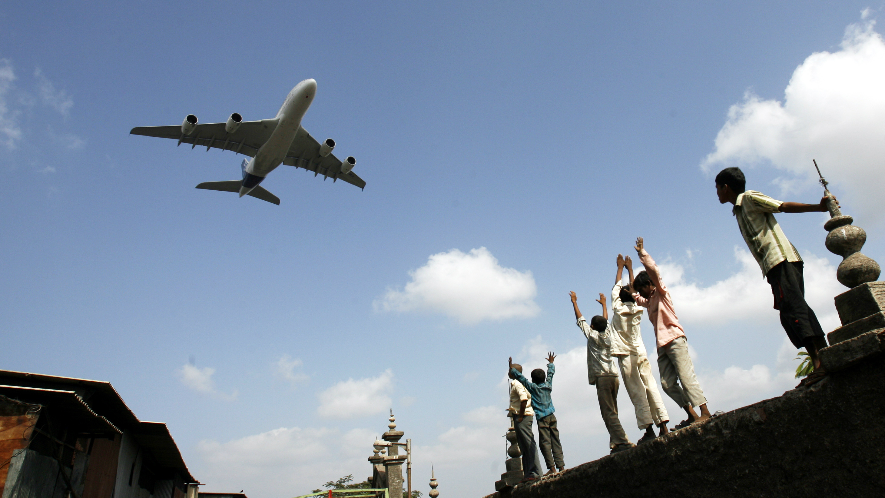 Children react as an Airbus A380 aircraft flies over them near Mumbai airport May 8, 2007. European plane-maker Airbus hopes to win 20 orders for its A380 this year and is in talks with new airlines in India to sell the plane, the world's largest passenger aircraft, a senior executive said on Monday. REUTERS/Arko Datta (INDIA)