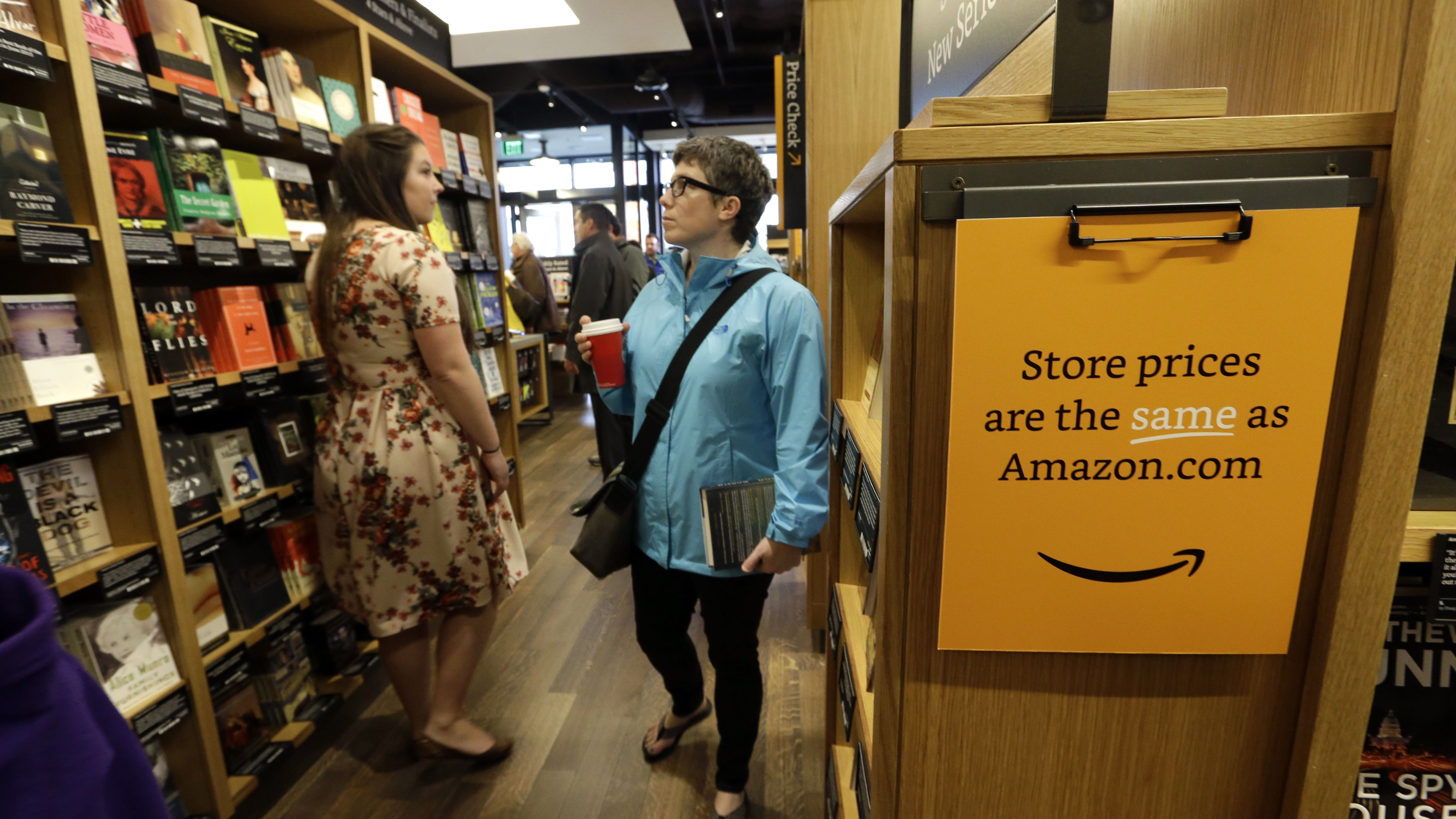 Customers browse aisles at the opening day for Amazon Books, the first brick-and-mortar retail store for online retail giant Amazon, Tuesday, Nov. 3, 2015, in Seattle. The company says the Seattle store, coming two decades after it began selling books over the Internet, will be a physical extension of its website, combining the benefits of online and traditional book shopping. (AP Photo/Elaine Thompson)