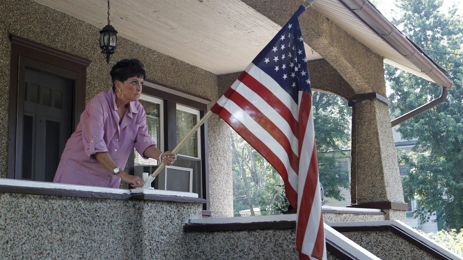 A woman places a US flag on her porch.