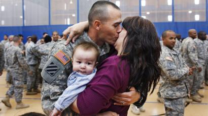 Soldier holding baby kisses wife.