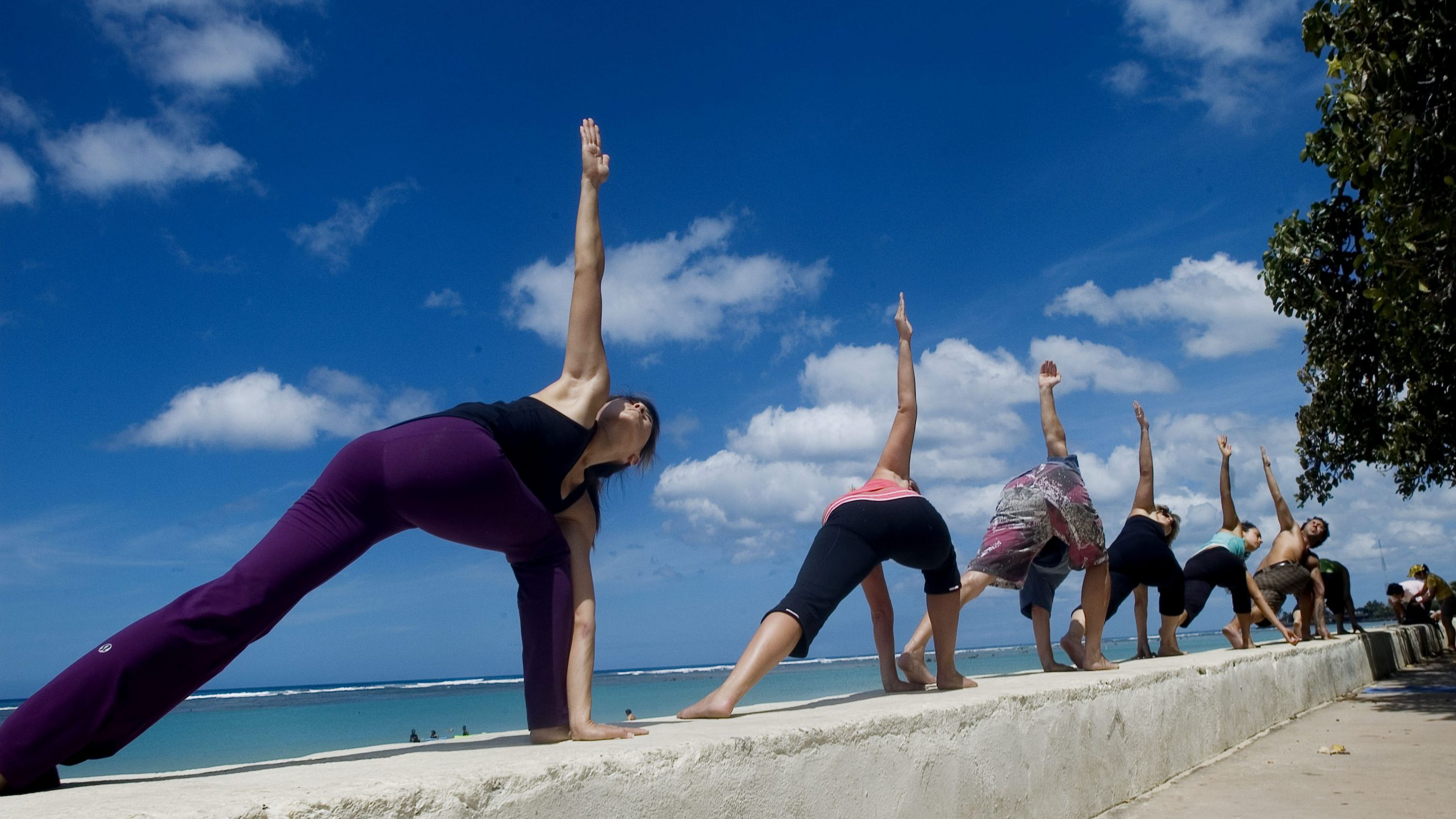 """Sommerlyn Leong left, and Keely Bruns, second from left, and others participate in a """"guerilla yoga"""" practice session alongside Ala Moana Beach, Sunday July 1, 2007, in Honolulu, Hawaii. The event is part of a series of """"random acts of yoga"""" in public places throughout Honolulu to bring awareness to yoga and physical fitness."""