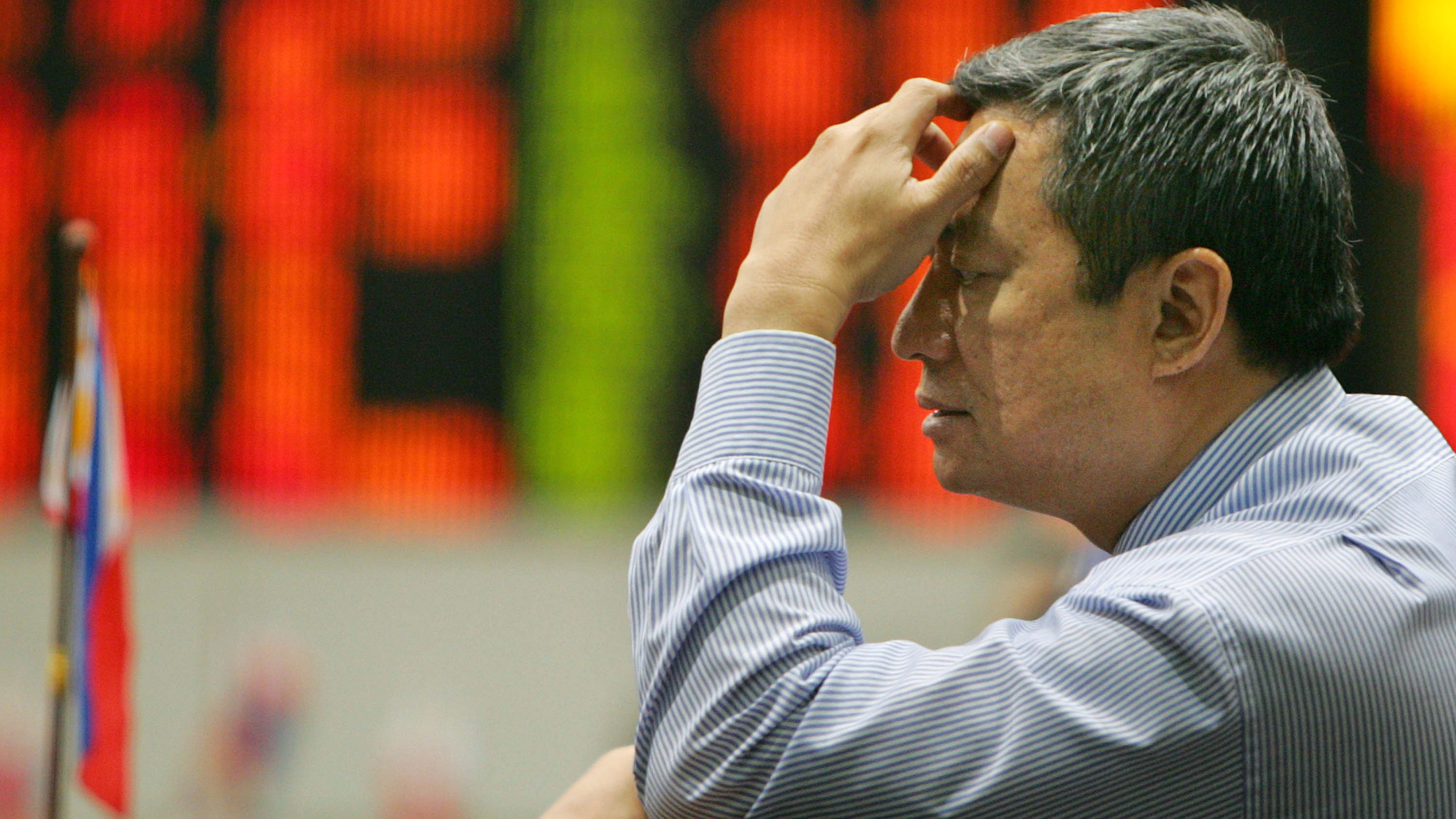 A trader contemplates as the electronic board shows figures in color red during trading at the Philippine Stock Exchange Tuesday, Sept. 30, 2008 in Manila's financial district of Makati. The composite index fell 37.93 points to 2,569.65 after plunging 6.0 percent in early trade with shares closing 1.4 percent lower following the the collapse of the Wall Street bailout package.