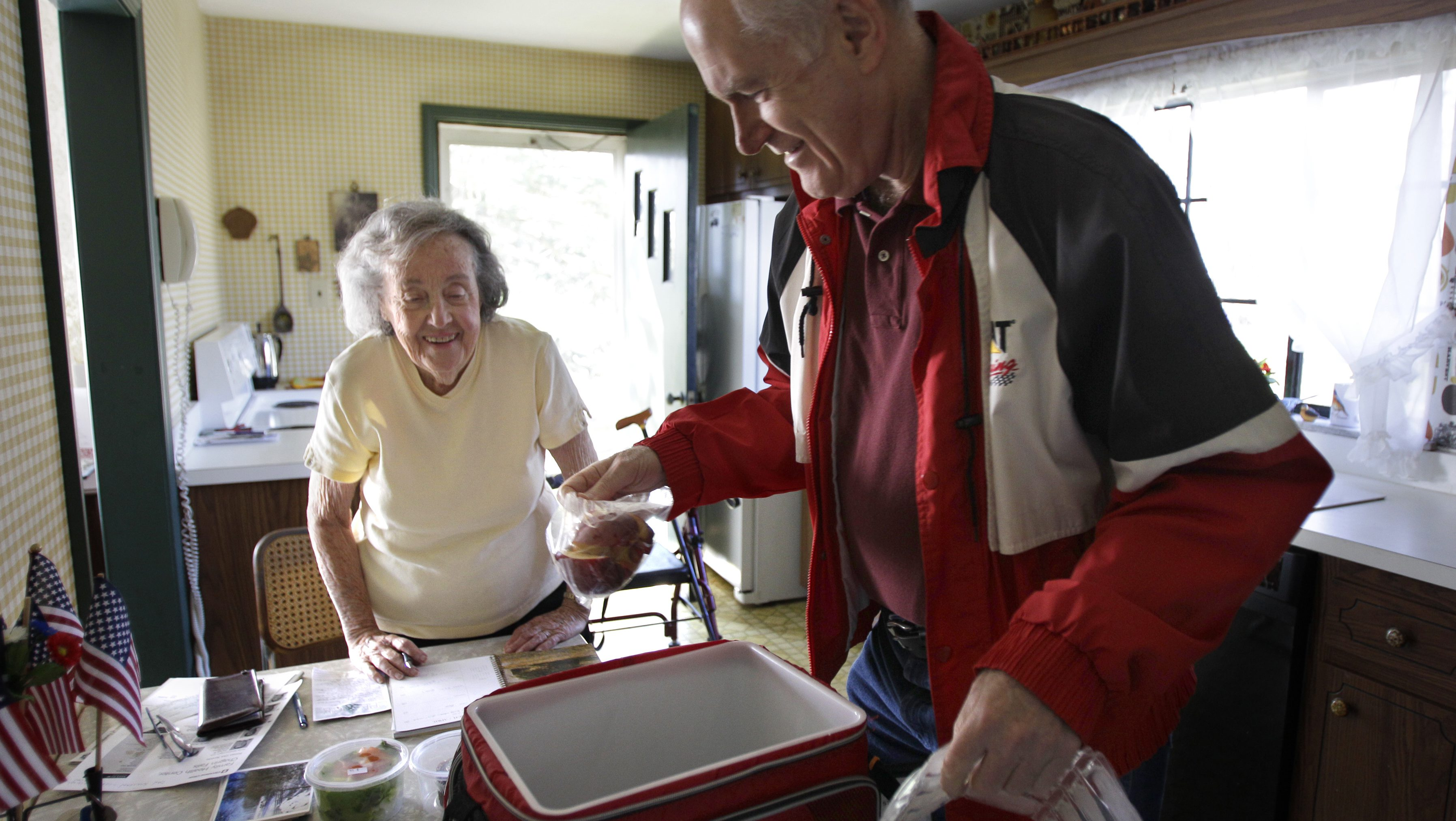Marty Robertson unpacks food from the Chagrin Falls Meals on Wheels program for recipient Bernadette Winko, 90, in her Bentleyville, Ohio home on Wednesday,  March 14, 2012.  While Ohio's population growth has been nearly flat, the number of residents 65 and older has increased at a rate of nearly 8 percent, underscoring the growing need for senior services. Many Ohio counties are investing in in-home help, like Meals on Wheels,  aimed at enabling older residents to age in their own homes. (AP Photo/Amy Sancetta)