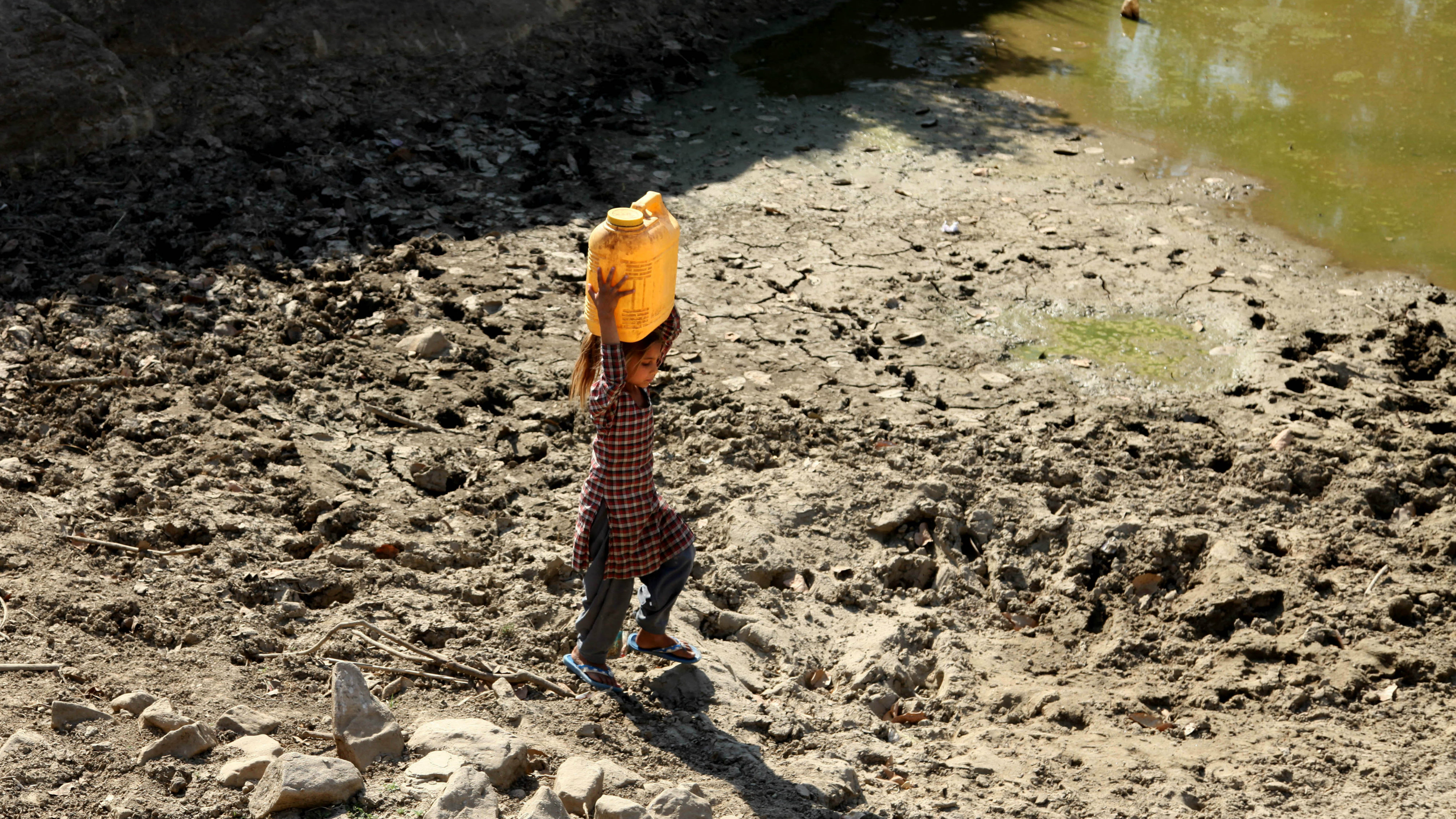 In this Friday, April 29, 2016, file photo, an Indian girl carries drinking water in a plastic container on her head as she walk back to her village after collecting it from an almost dried up well in Samba district, some 40 kilometres (25 miles) from Jammu, India. Much of India is reeling under a weeks long heat wave and severe drought conditions that have decimated crops, killed livestock and left at least 330 million Indians without enough water for their daily needs.